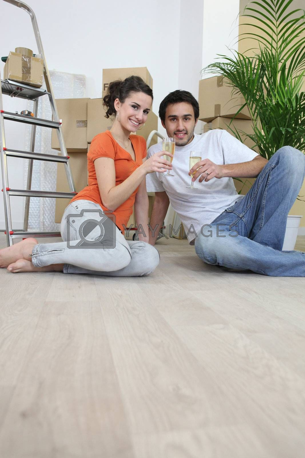 Couple sat on flooring toasting