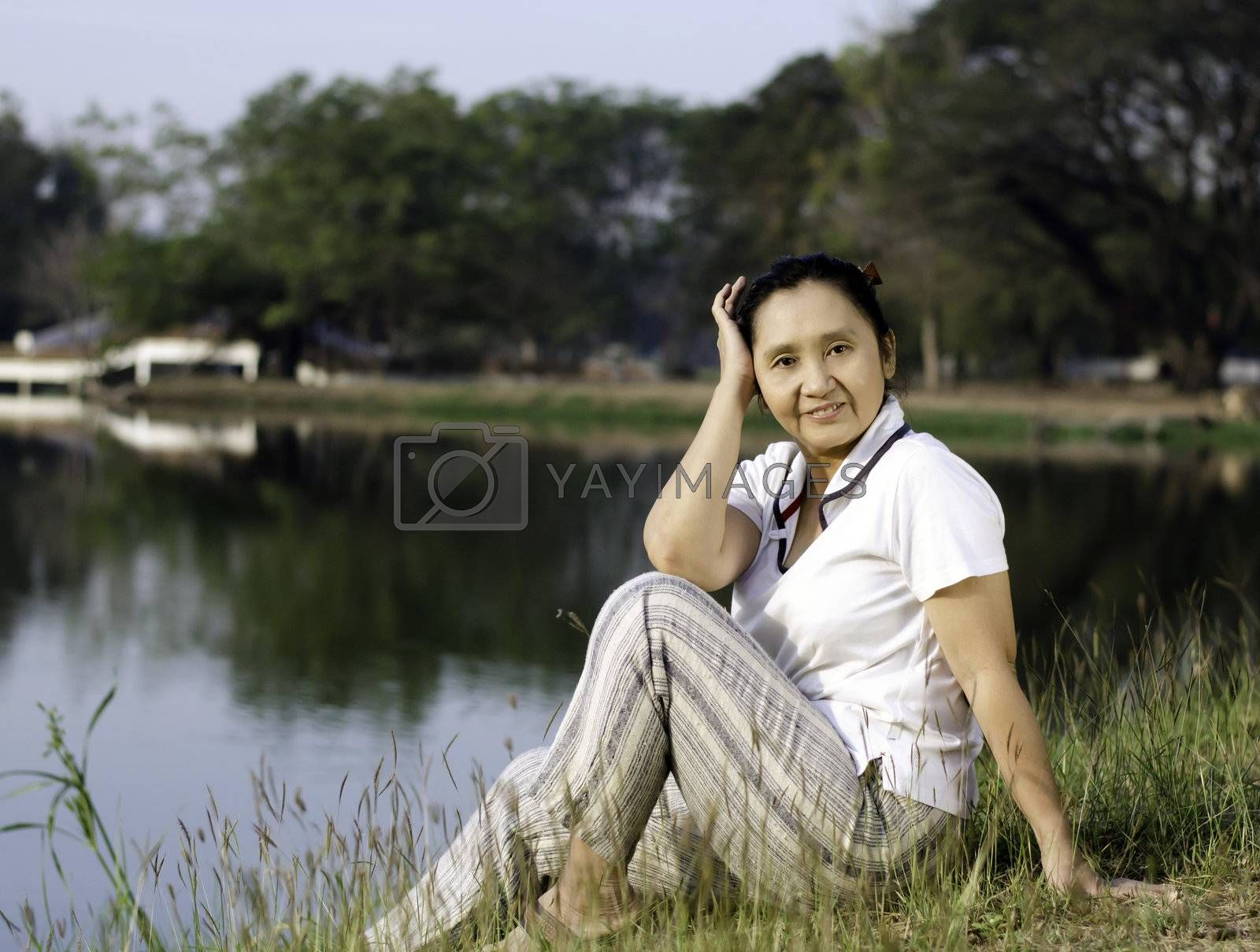 Sitting asian woman by lake