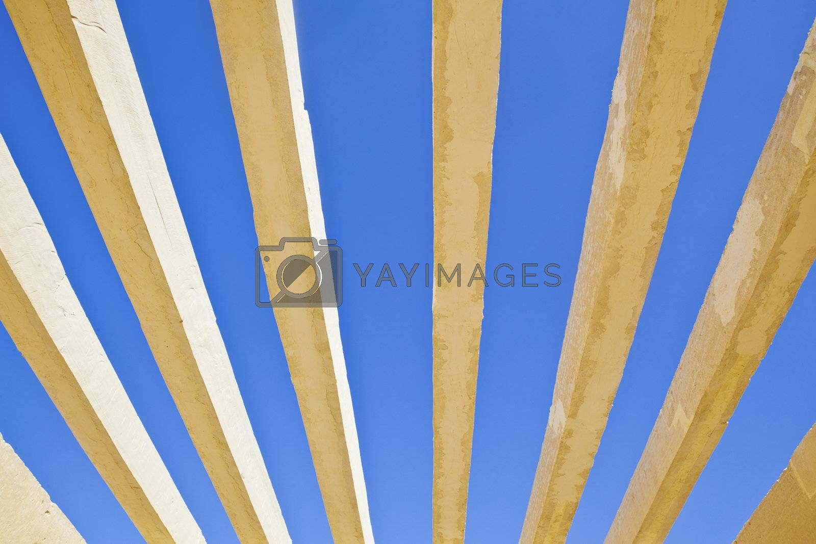 Horizontal detail of architecture to the roof of the public access to Shree Dwarakadheesh Krishna Temple at Dwarka Gujarat India. With no shelter creats an abstract patten of the concrete box work against the rich blue sky withour clouds