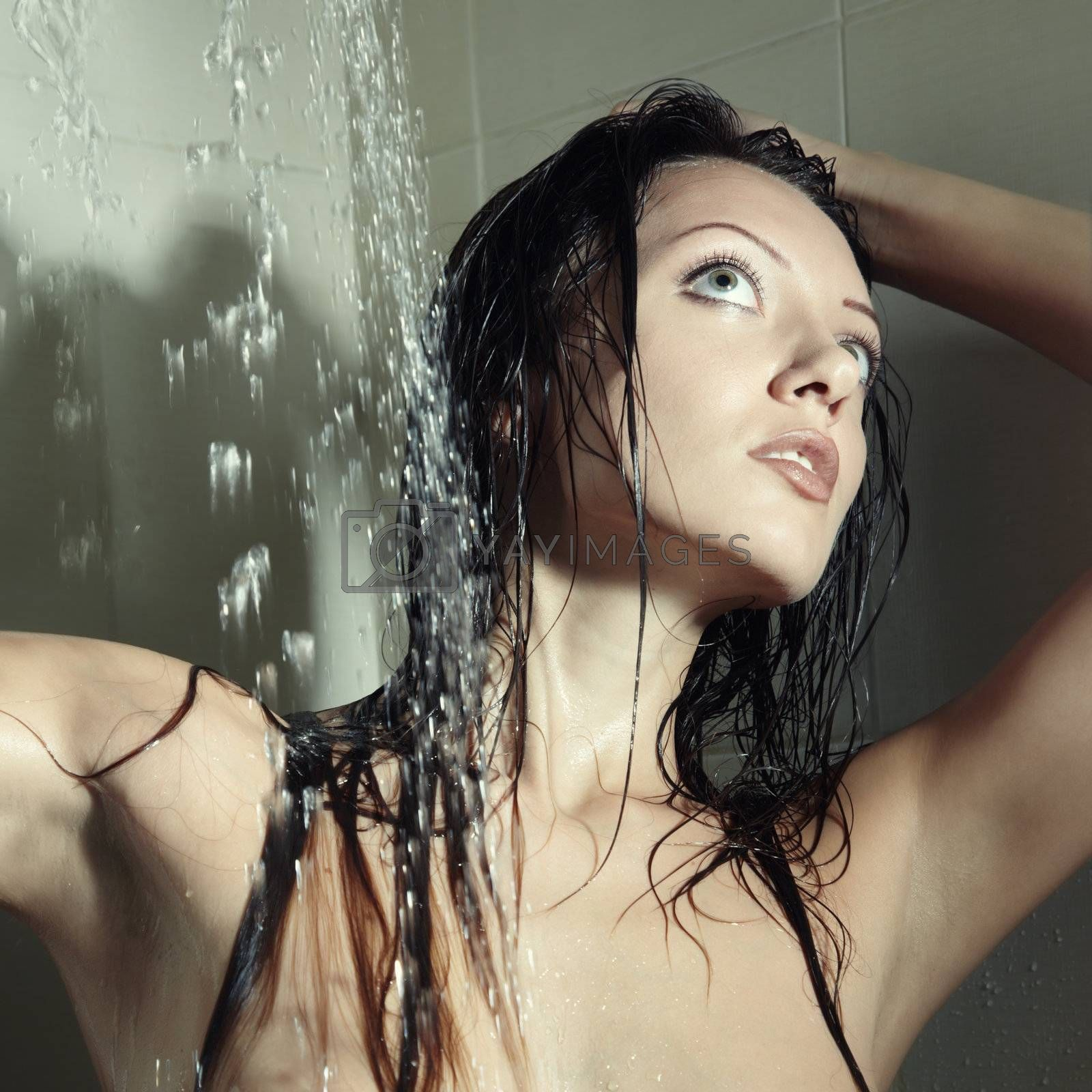 Wet attractive young lady in the bathroom under the water from shower