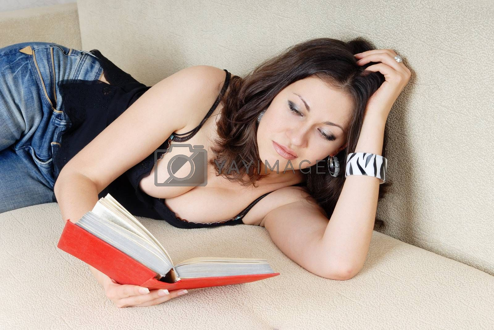 Sad attractive lady laying on a sofa and reading the love novel