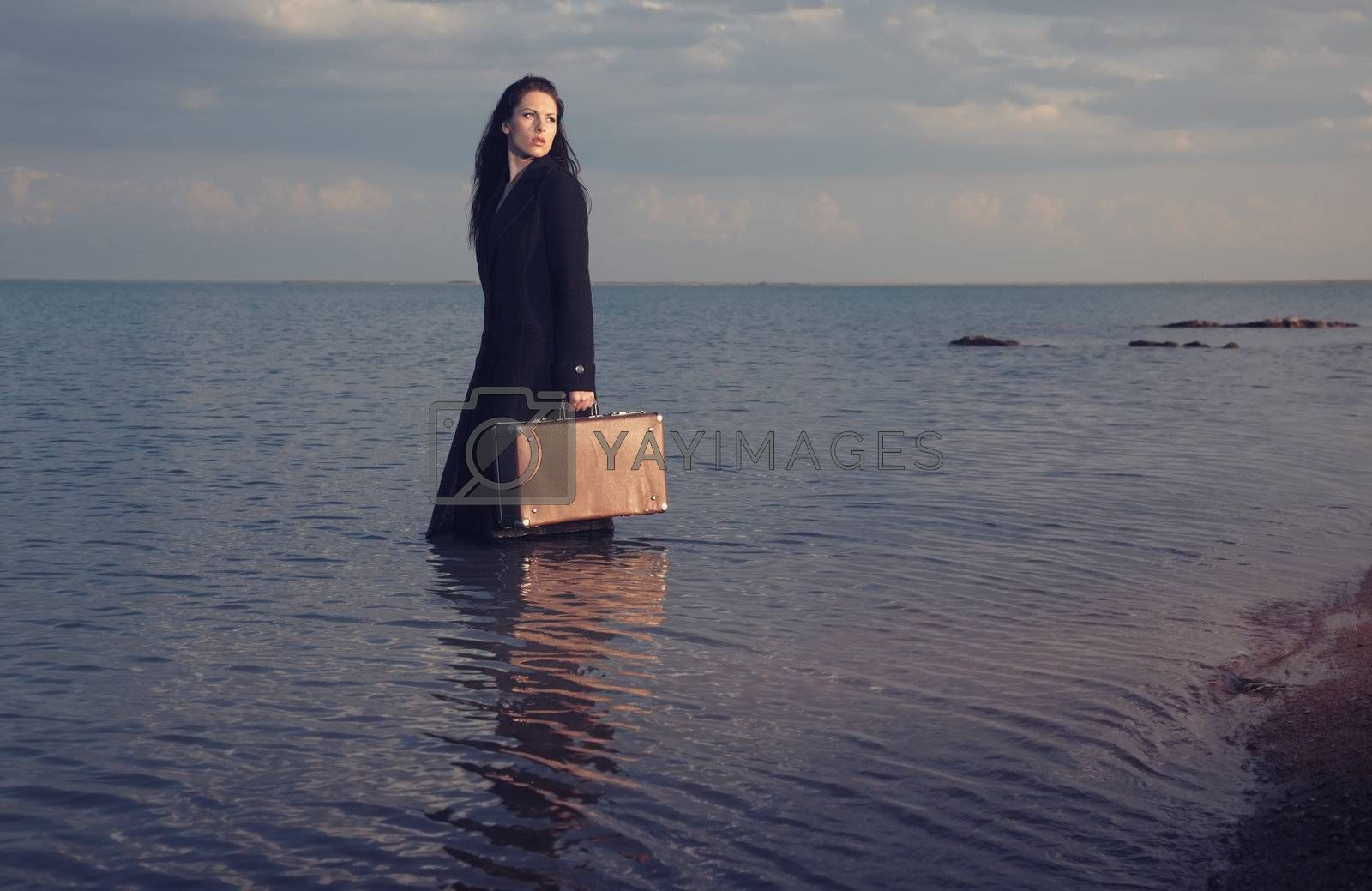 Lady in coat standing in the sea with travel bag