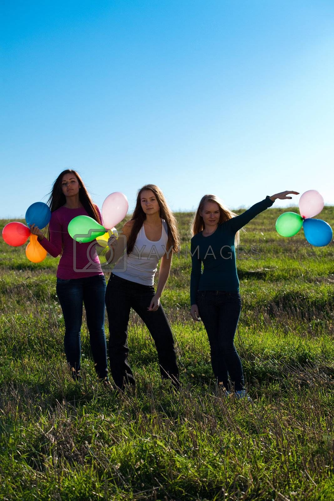 Royalty free image of three young beautiful woman with balloons into the field against by jannyjus
