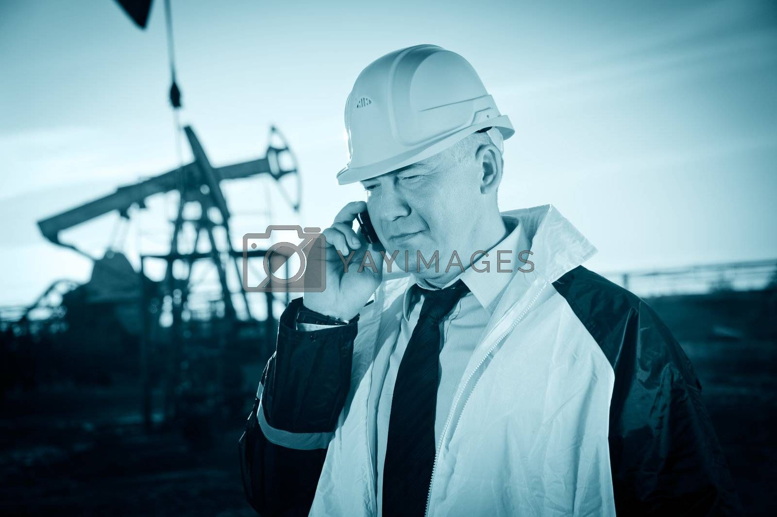 Oil worker in uniform and helmet, with mobile phone on of background the pump jack and sky. Toned.