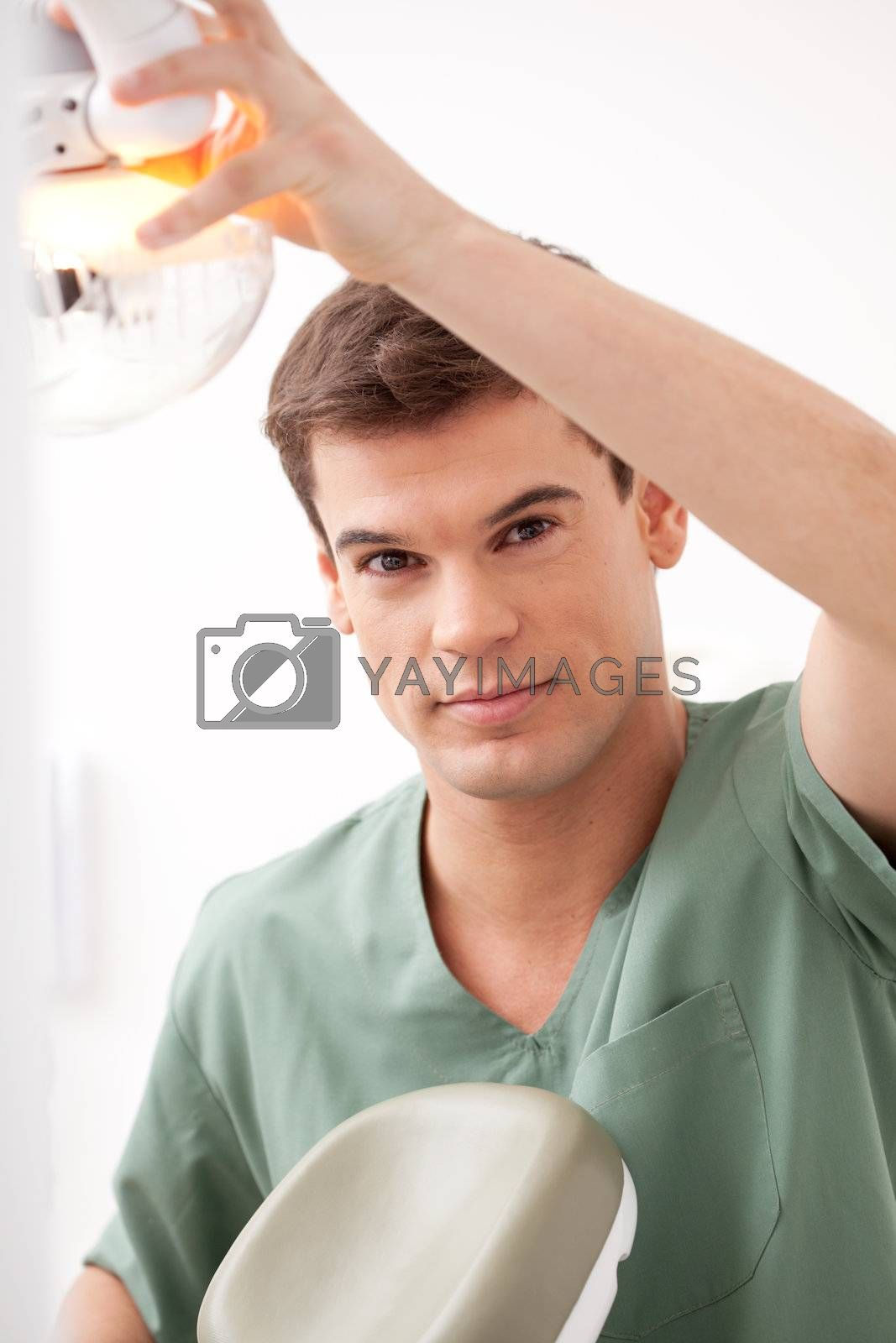 Portrait of a happy smiling male dentist adjust the light and chair