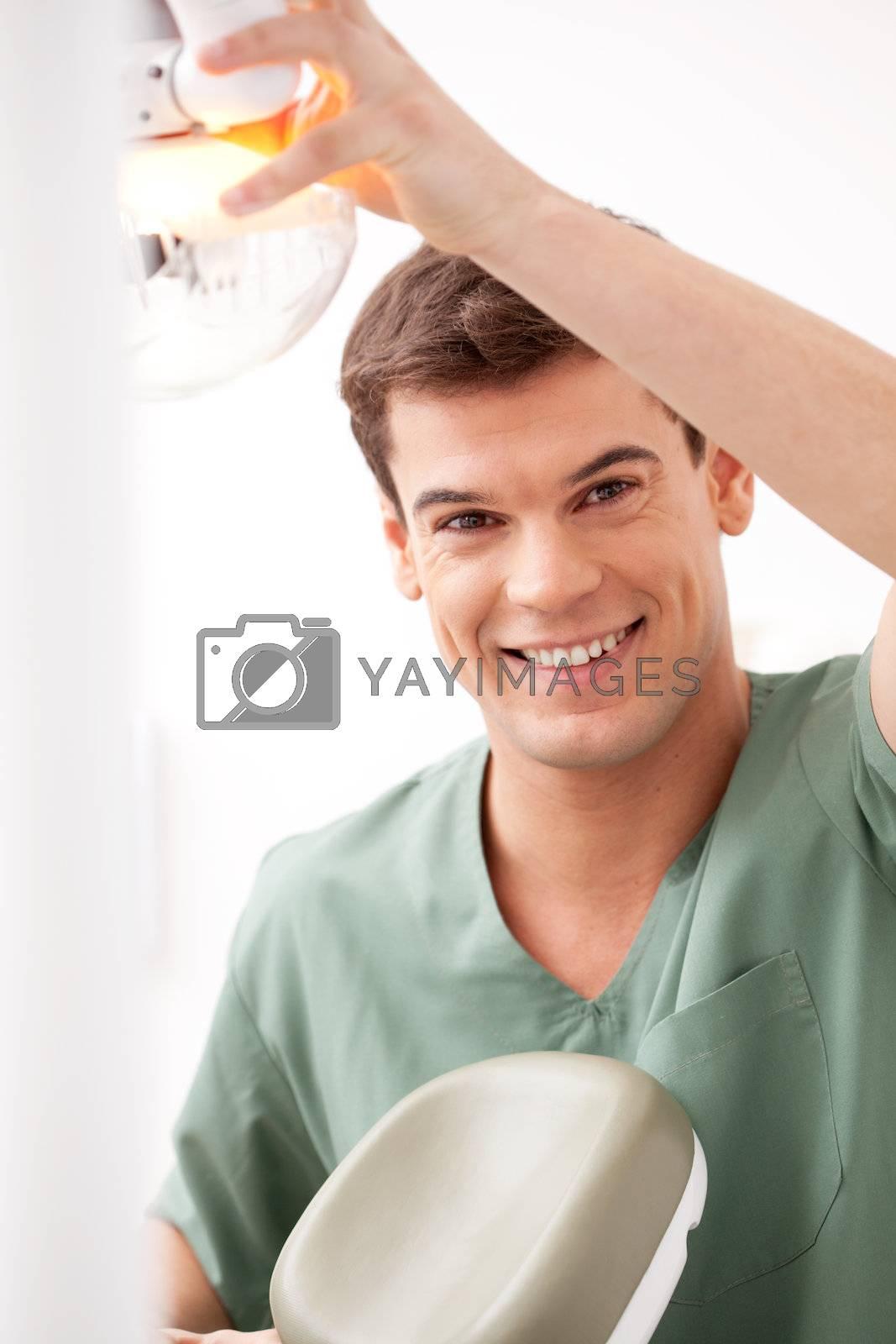 Happy smiling dentist looking at camera adjusting light