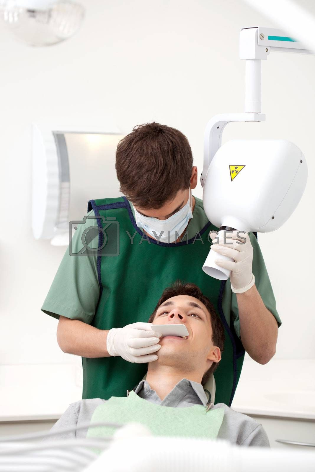 Dentist preparing x-ray machine on young male patient