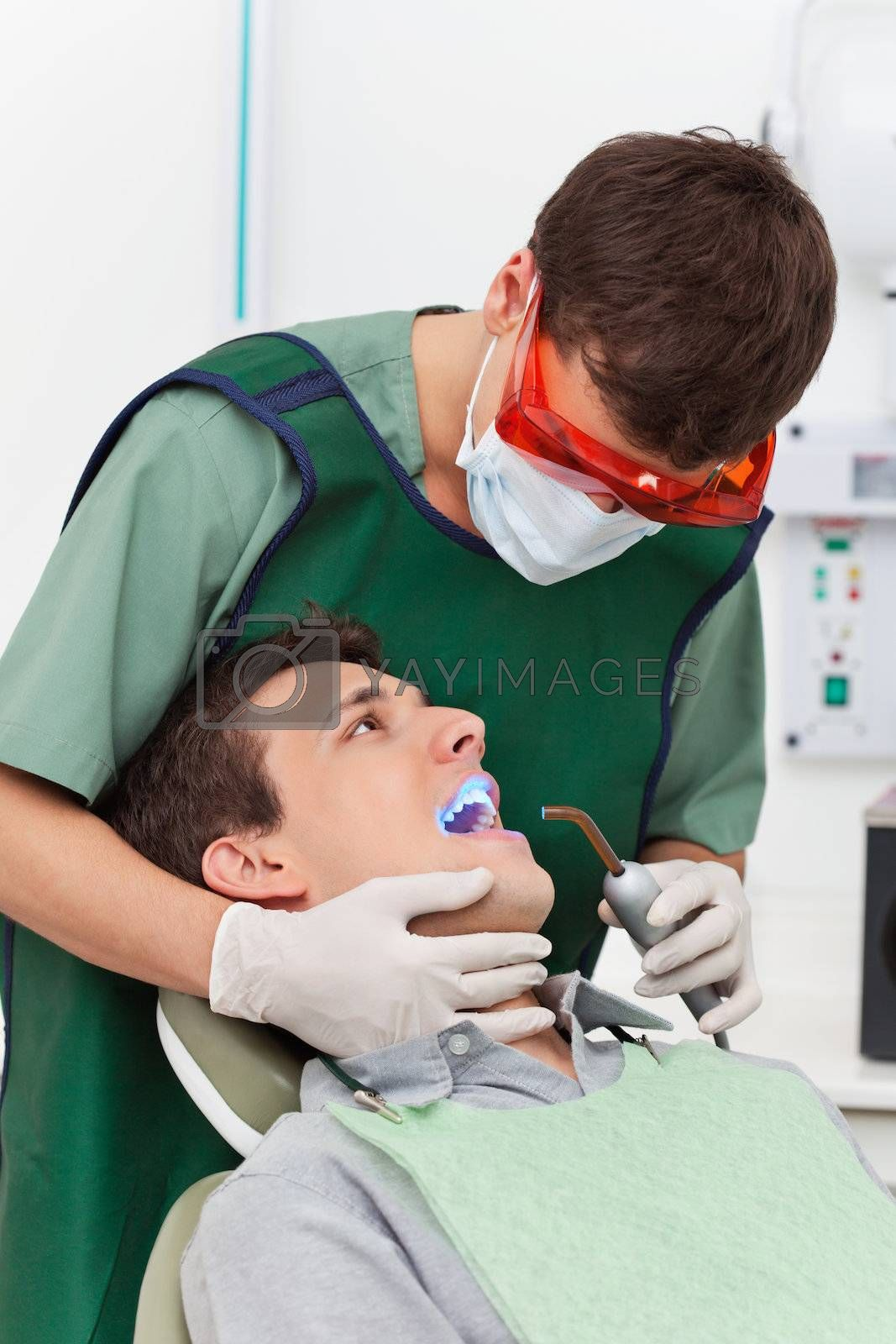 Young man going through therapy of tooth in clinic