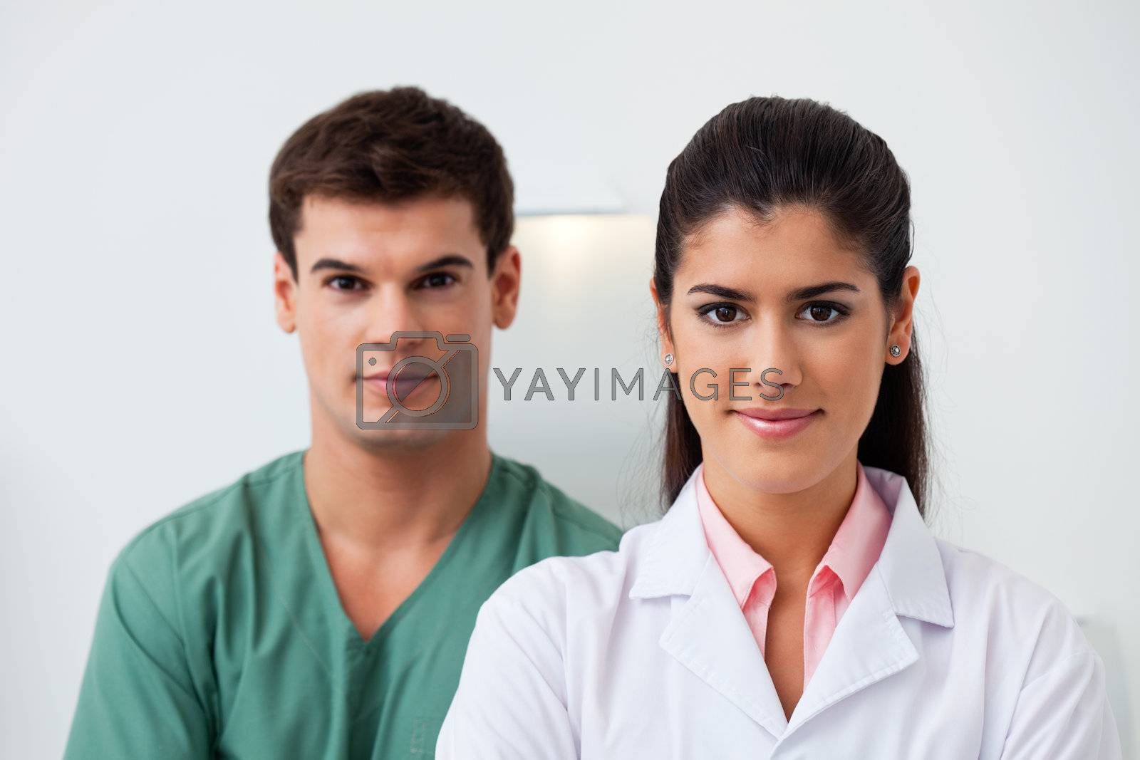 Portrait of female dentist standing with her assistant