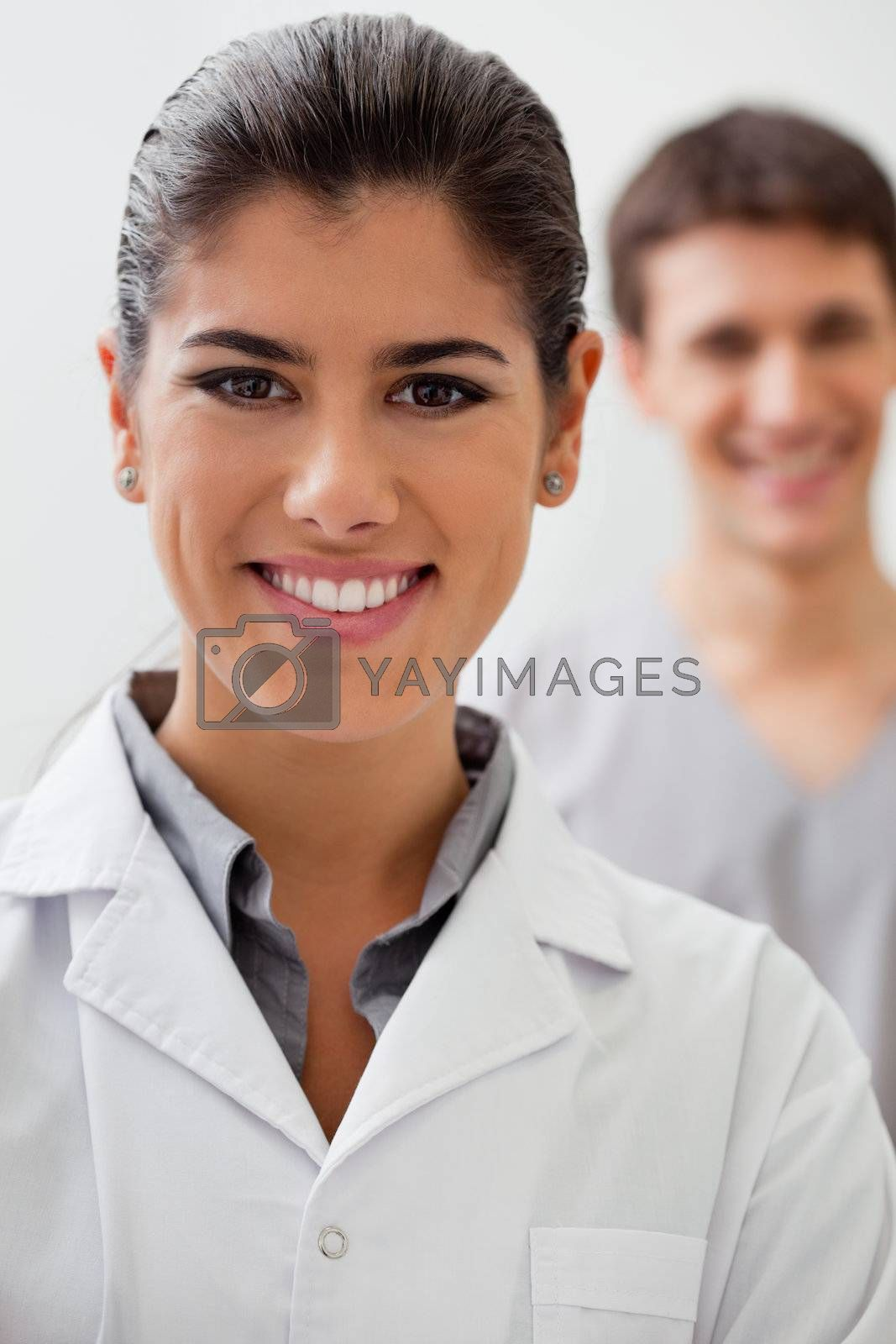 Portrait of happy female doctor with practitioner standing in background