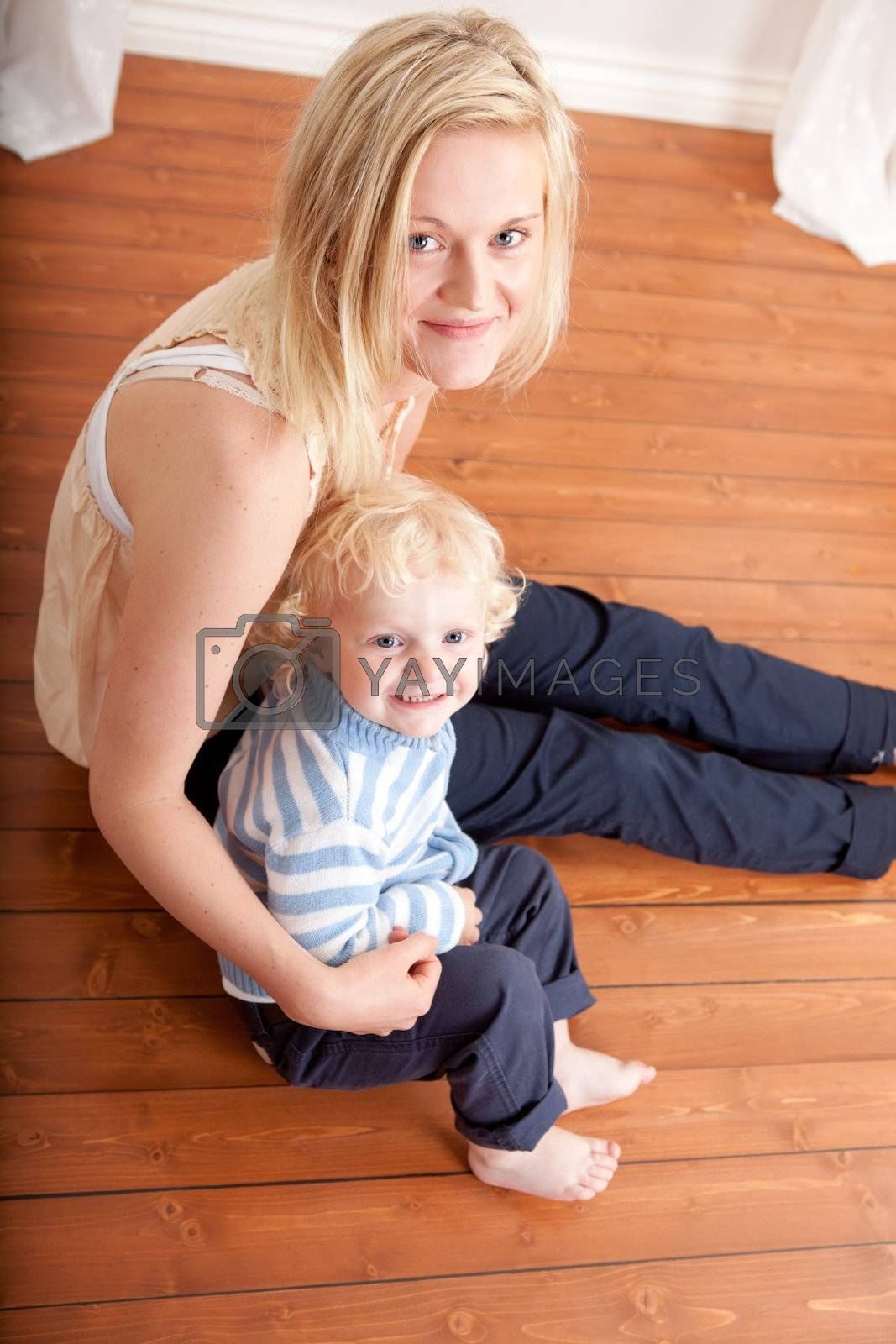 Mother with her toddler son looking at the camera from the floor