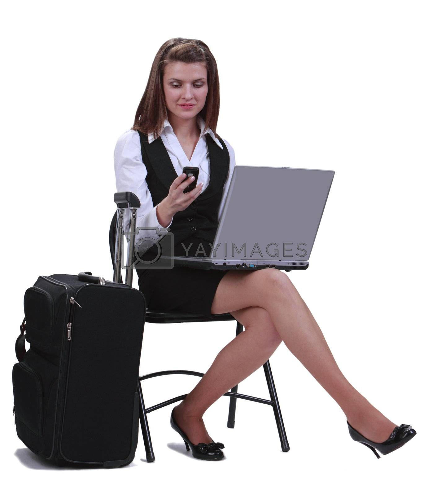 Young businesswoman reading a phone message while she is sitting with her laptop next to her suitcase,isolated against a white background.
