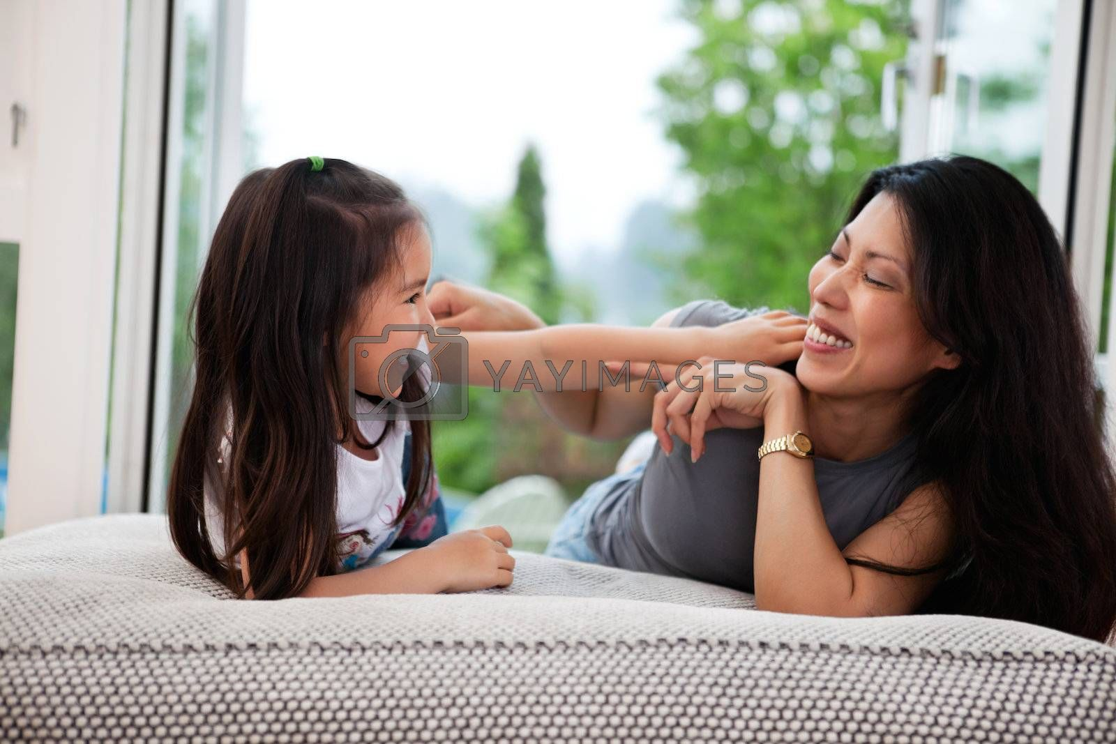 Portrait of happy mother and her daughter playing on couch