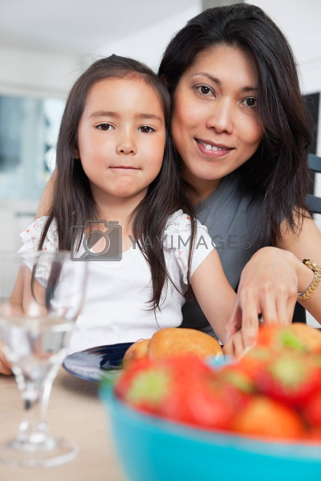 Portrait of mother and her cute daughter sitting at table