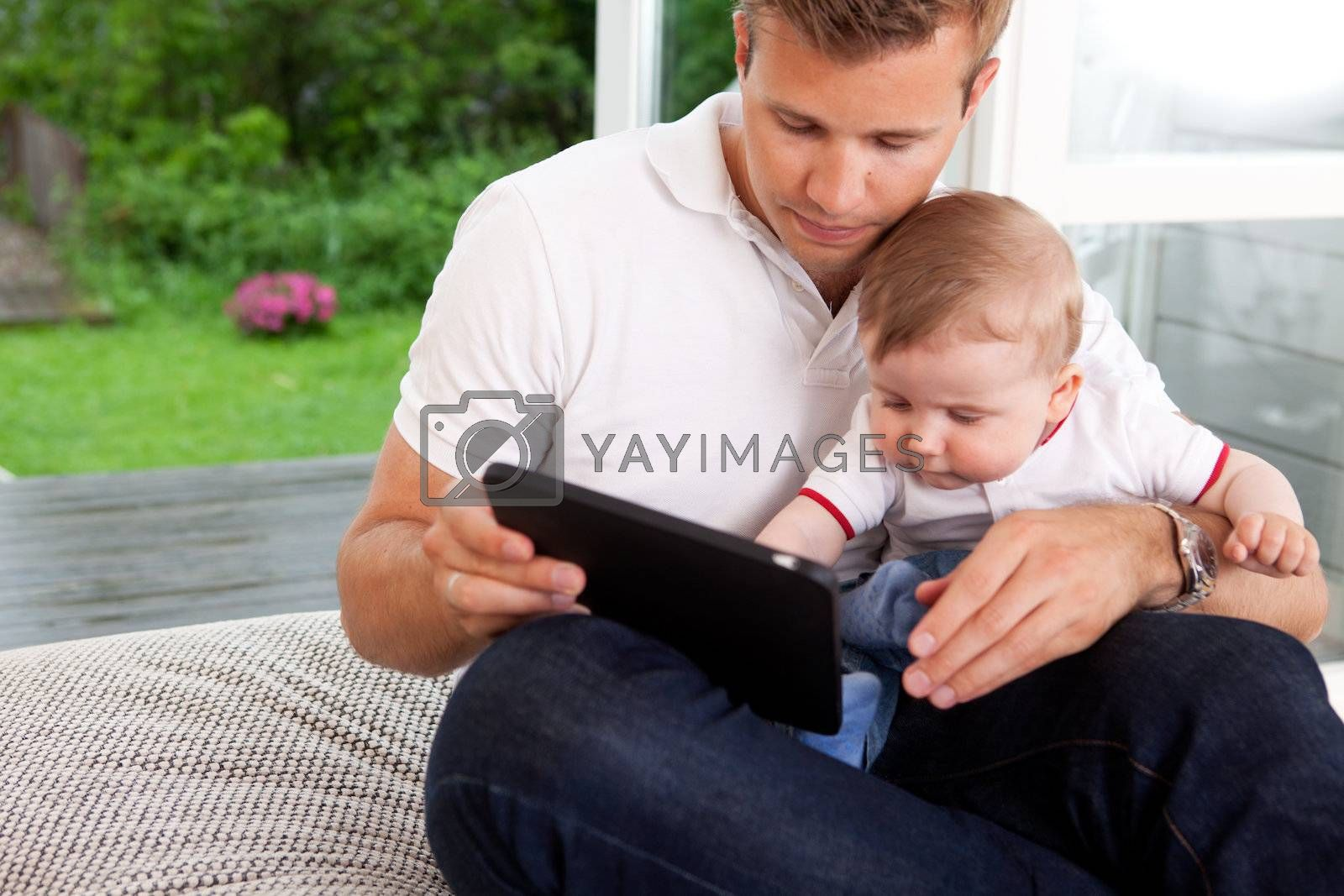 A father and son using a digital tablet in a home interior