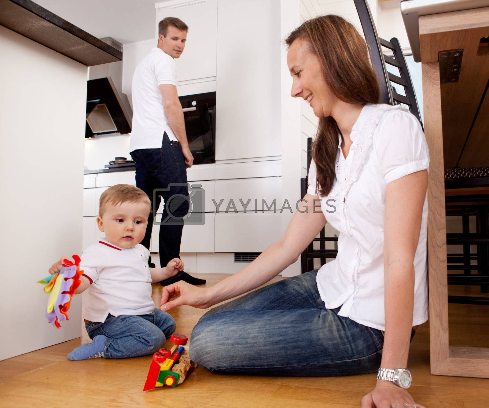 Mother playing with son on kitchen floor with father in background