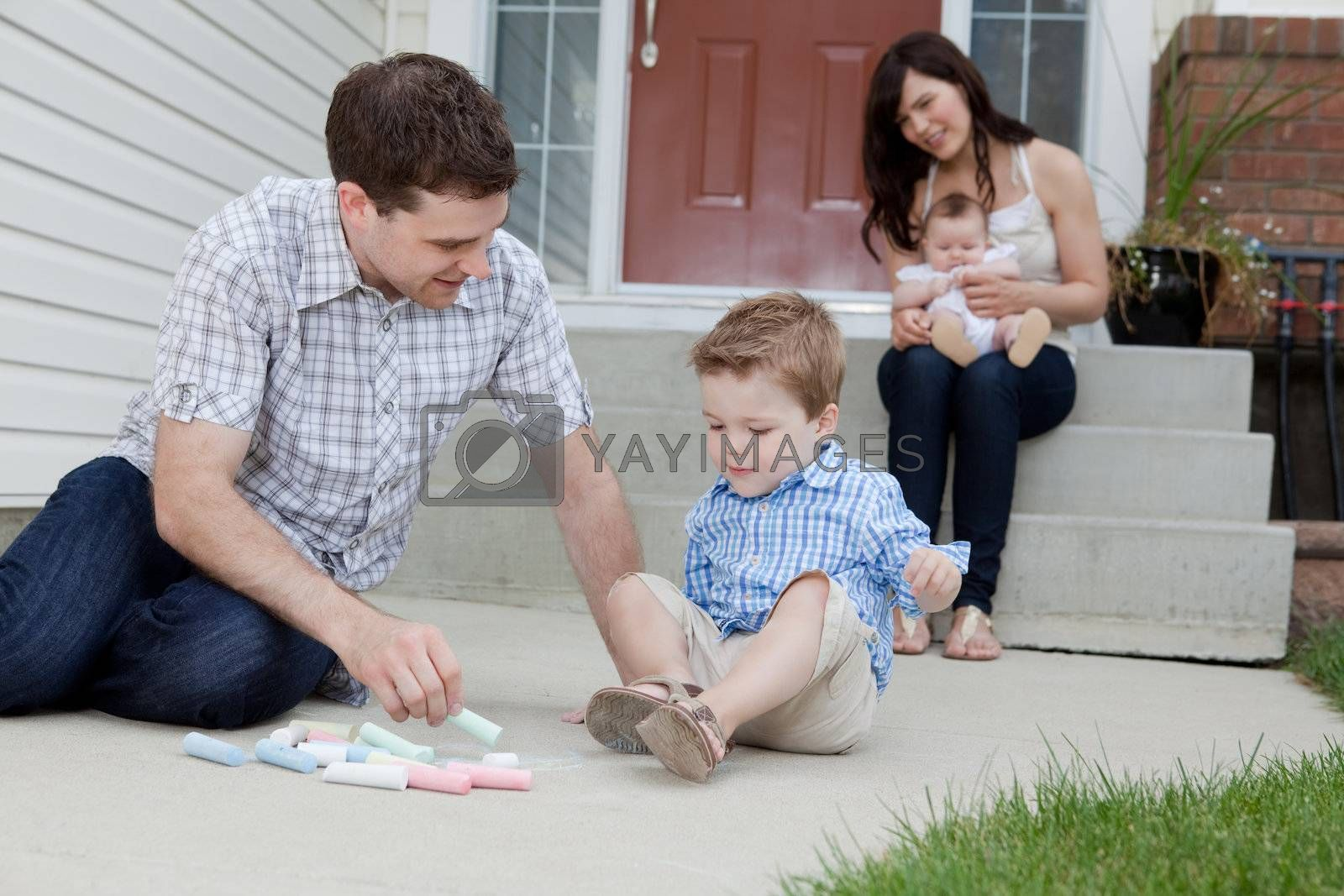 Young Father And Son Drawing With Chalk And Mother Sitting With Baby At Background In Front Of Their House.