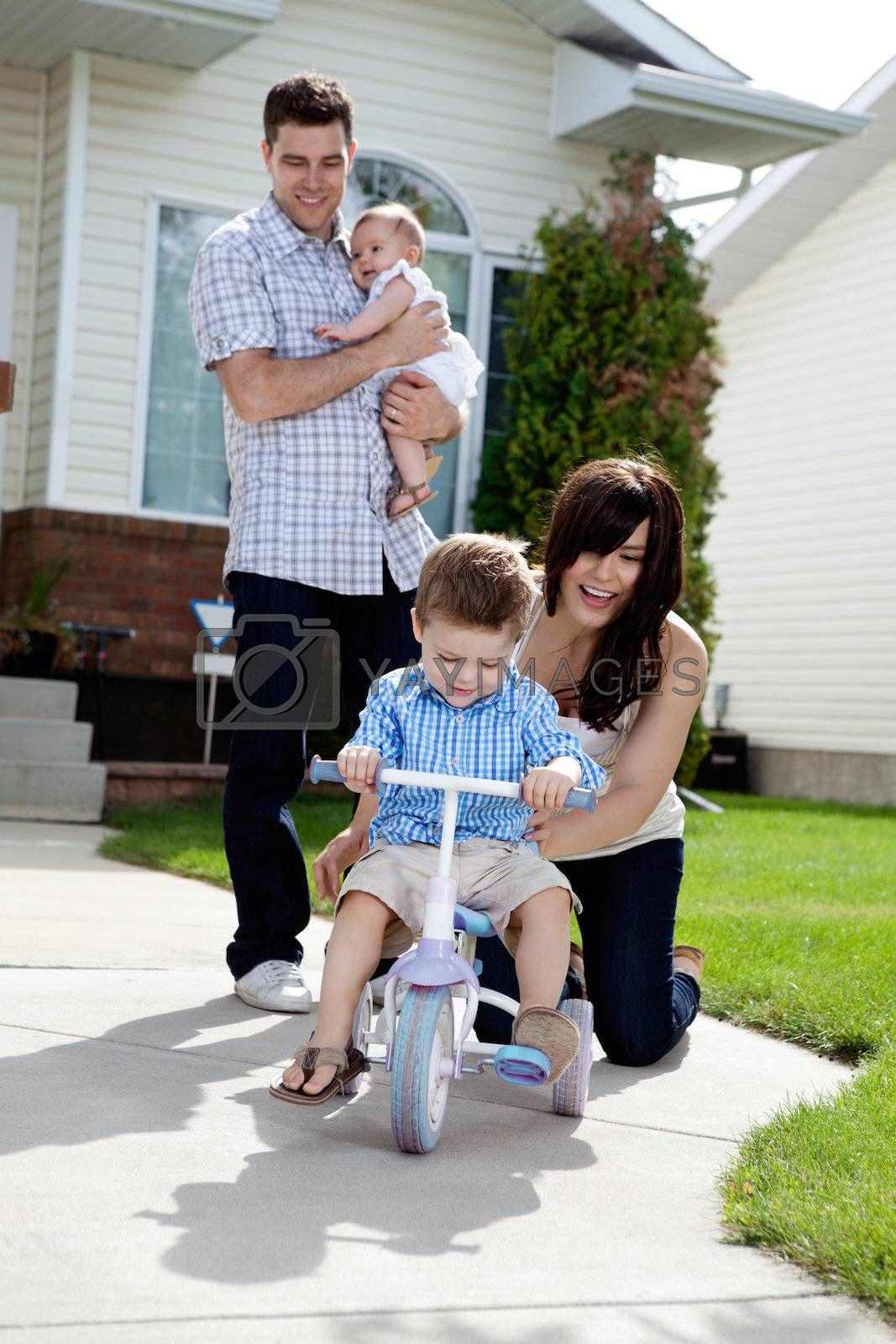 Cheerful Mother Teaching Son To Ride Tricycle by leaf