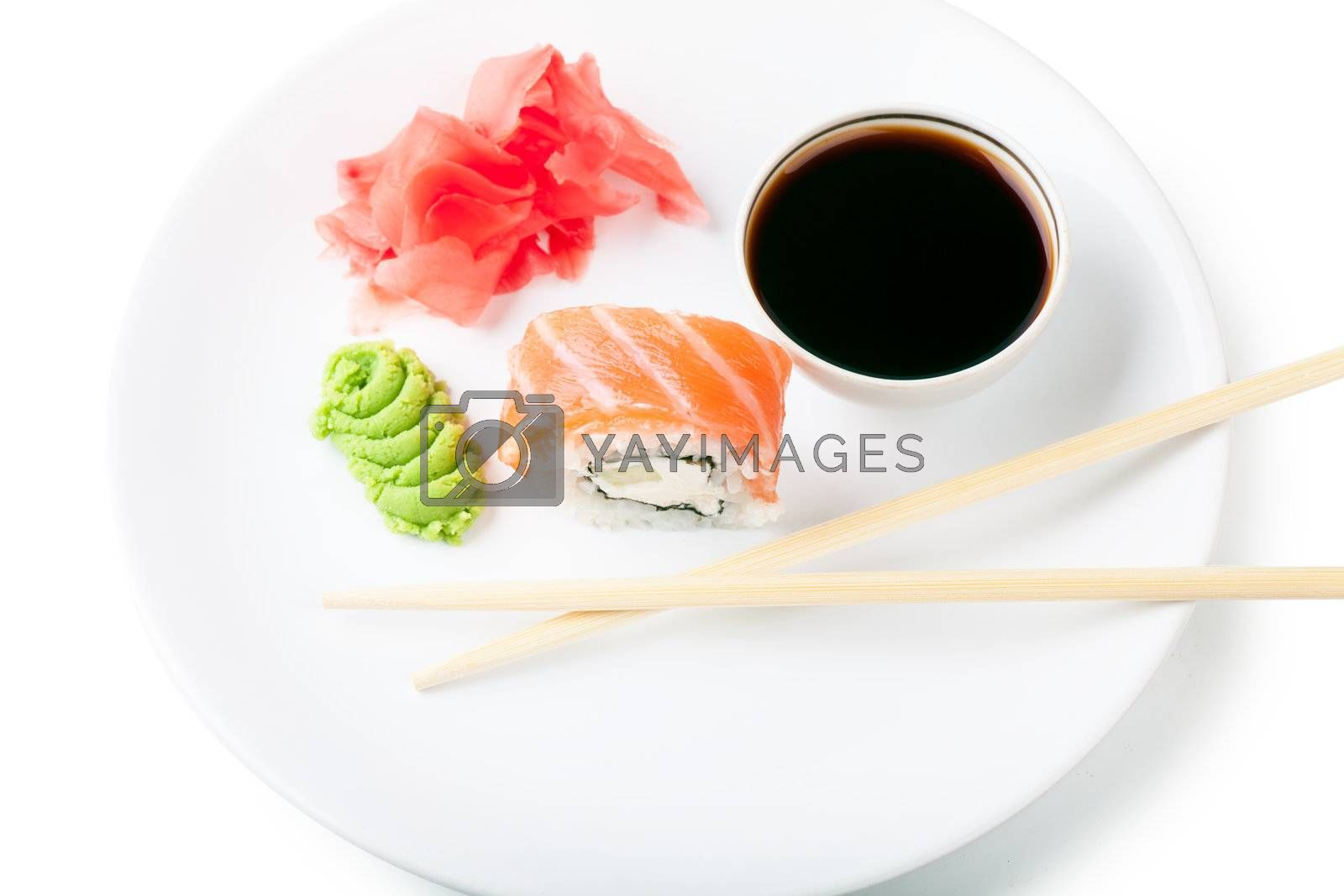 Sushi, soy and ginger with chopsticks on a white plate