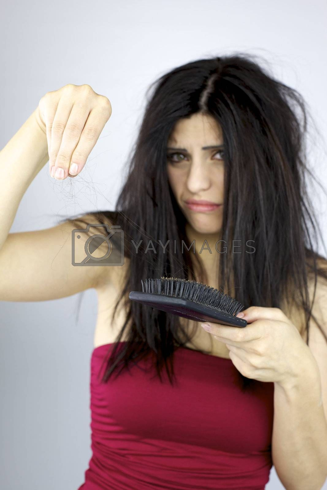 Unhappy woman holding lost hair in hand