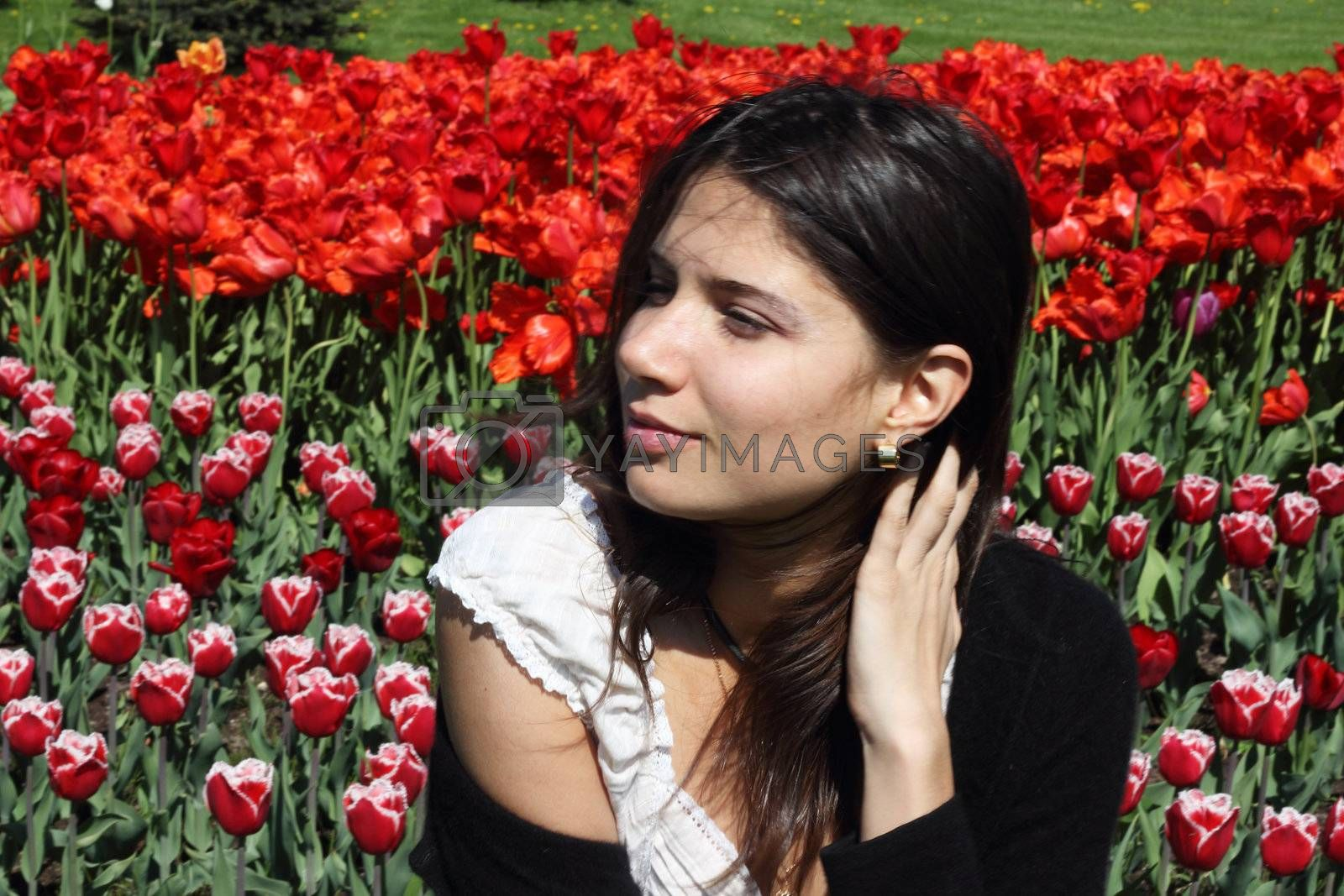 Portrait of a young woman on tulips background