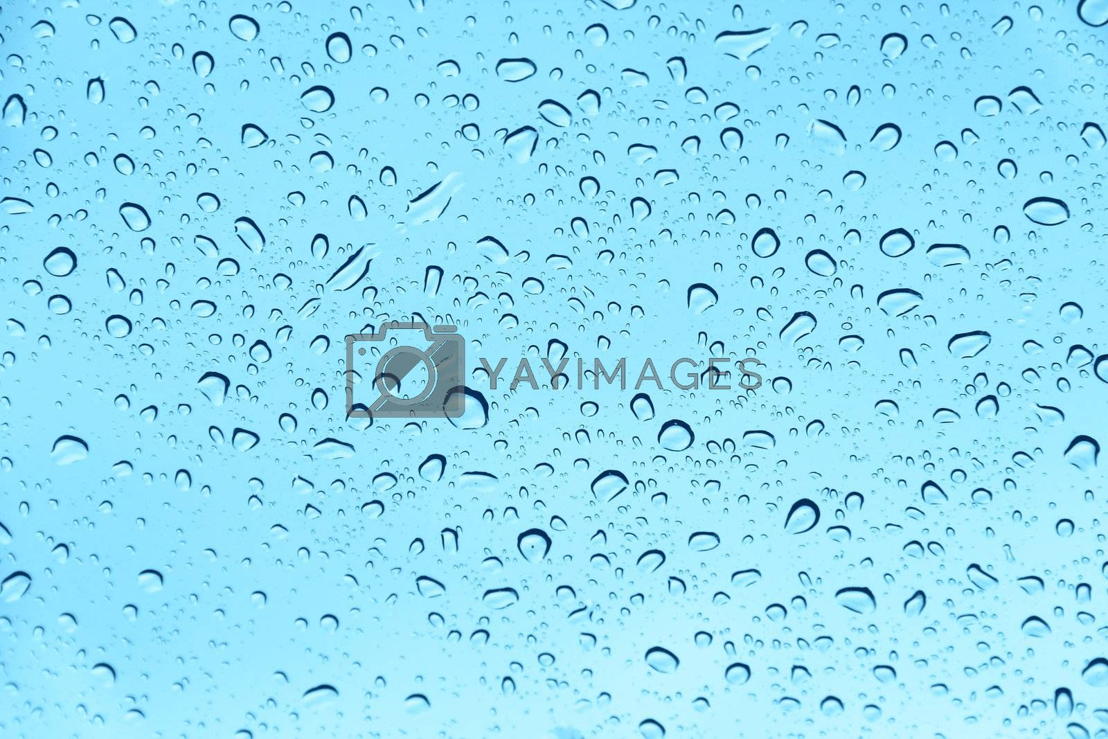 Water drops on blue transparent glass close up