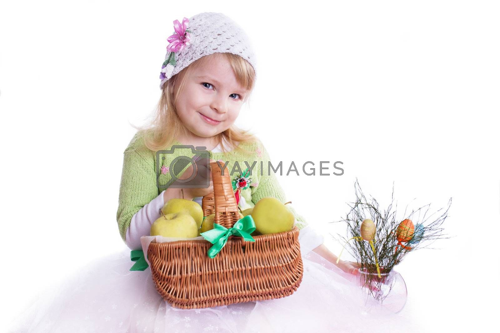 Smiling girl with basket full of apples and some flowers on white