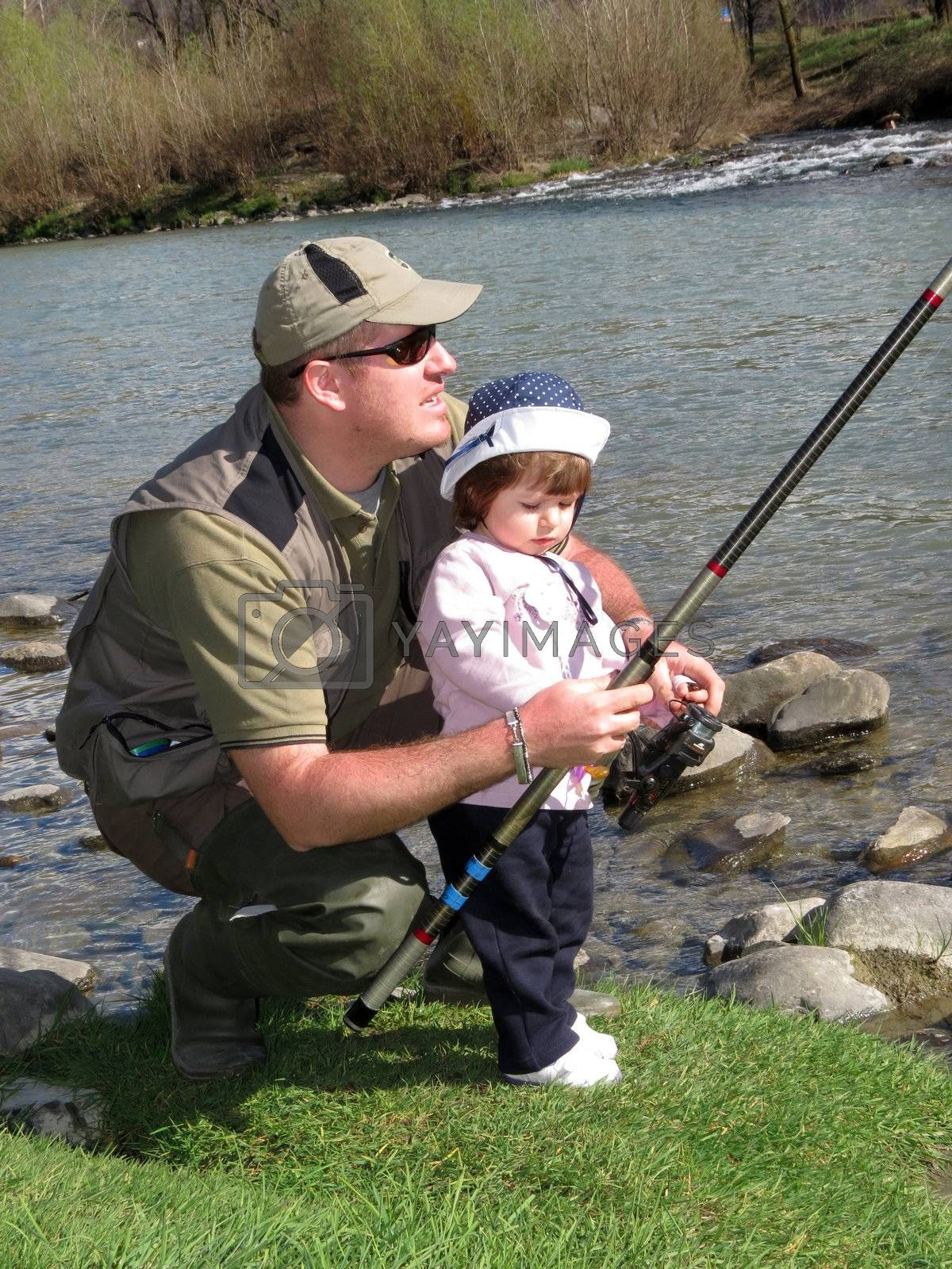 father and daughter fishing on river on summer day