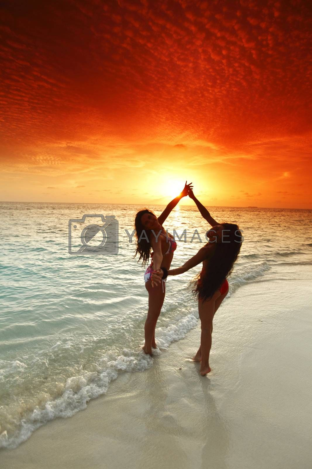 Two beautiful women in bikini enjoying sunset on beach