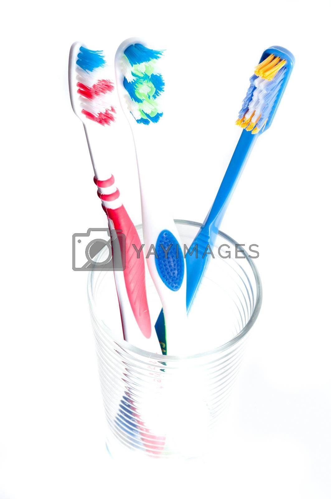 colorful toothbrushes in a glass over white