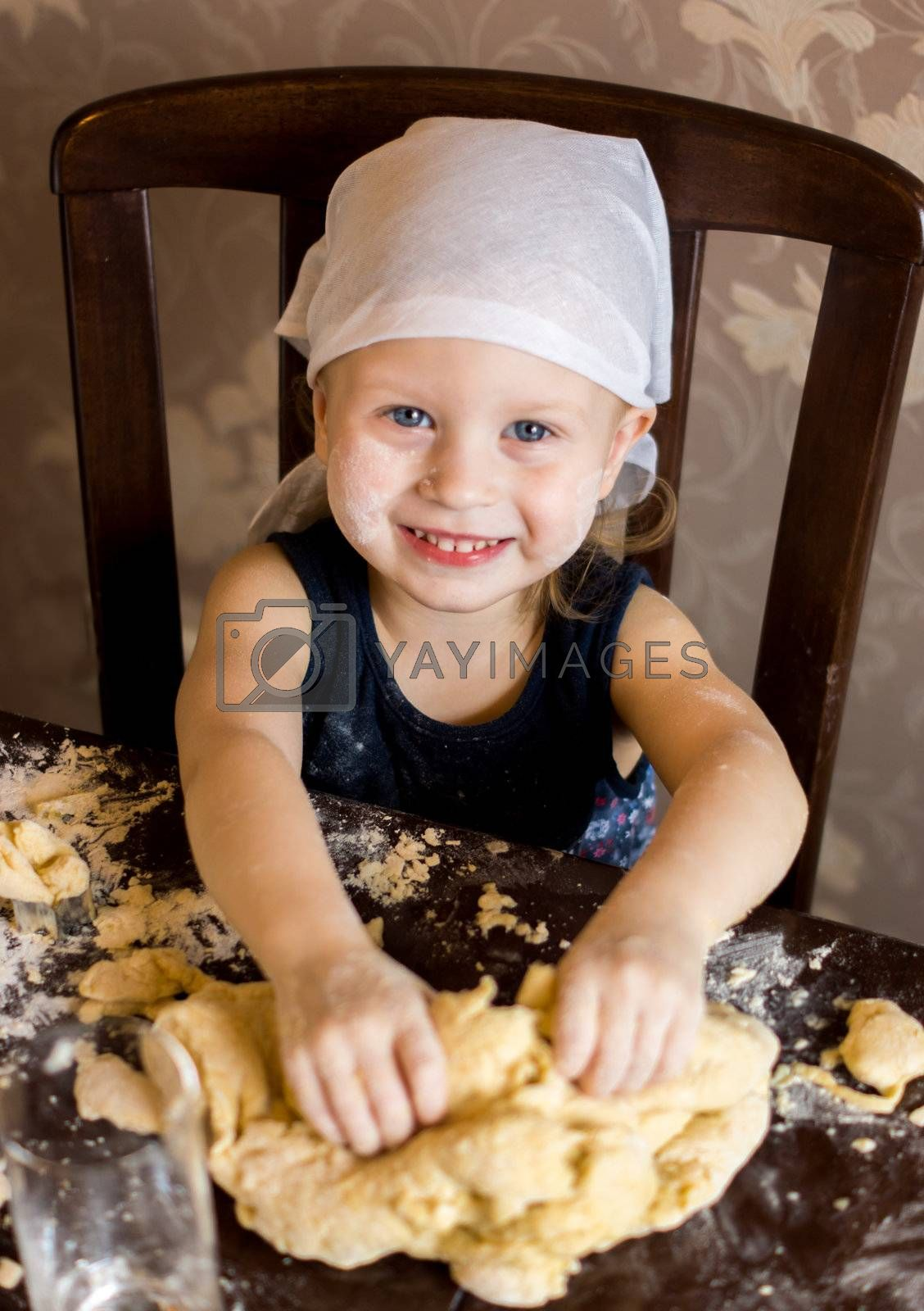 pretty little girl having fun kneads dough