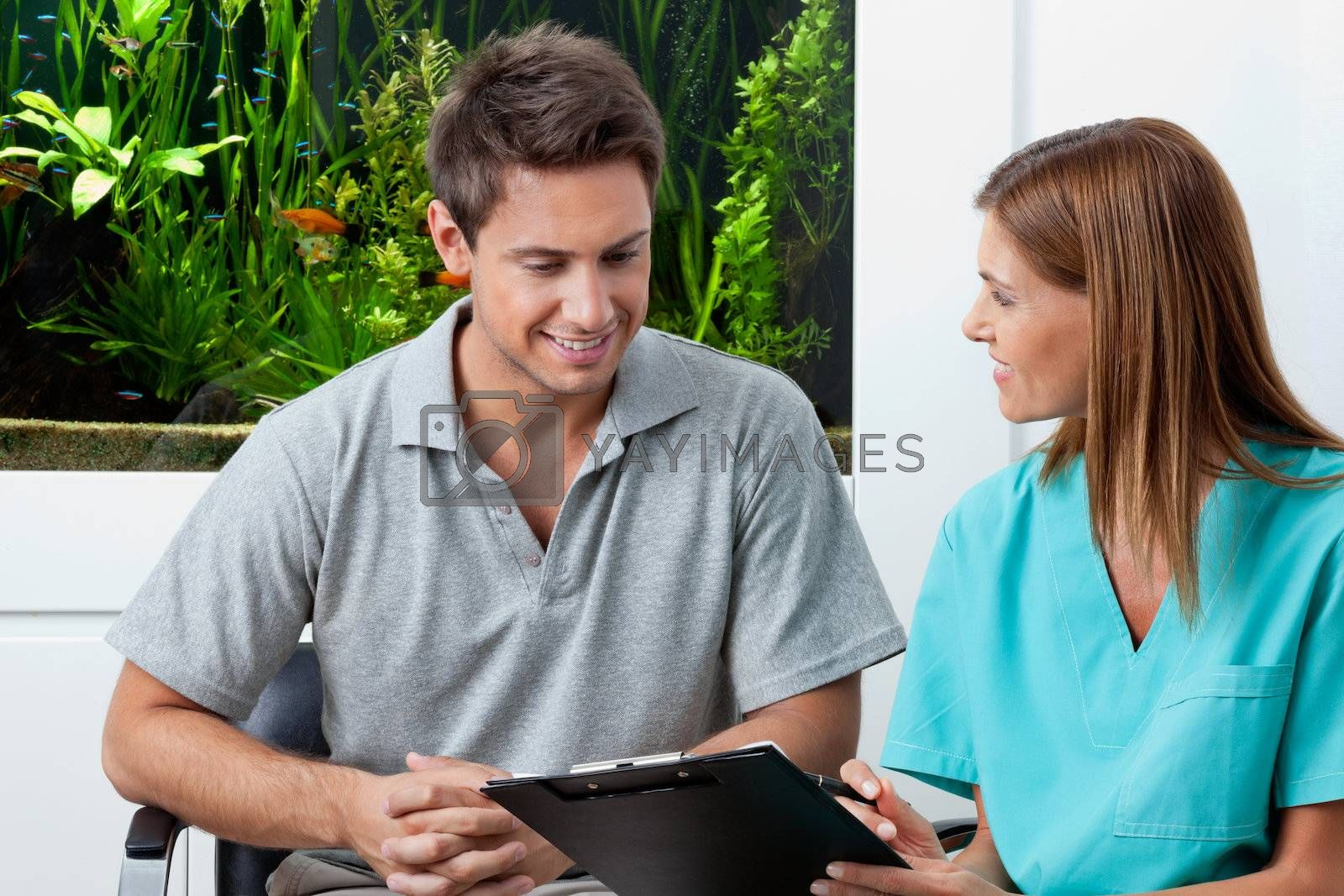 Female dentist with clipboard explaining something to man in clinic