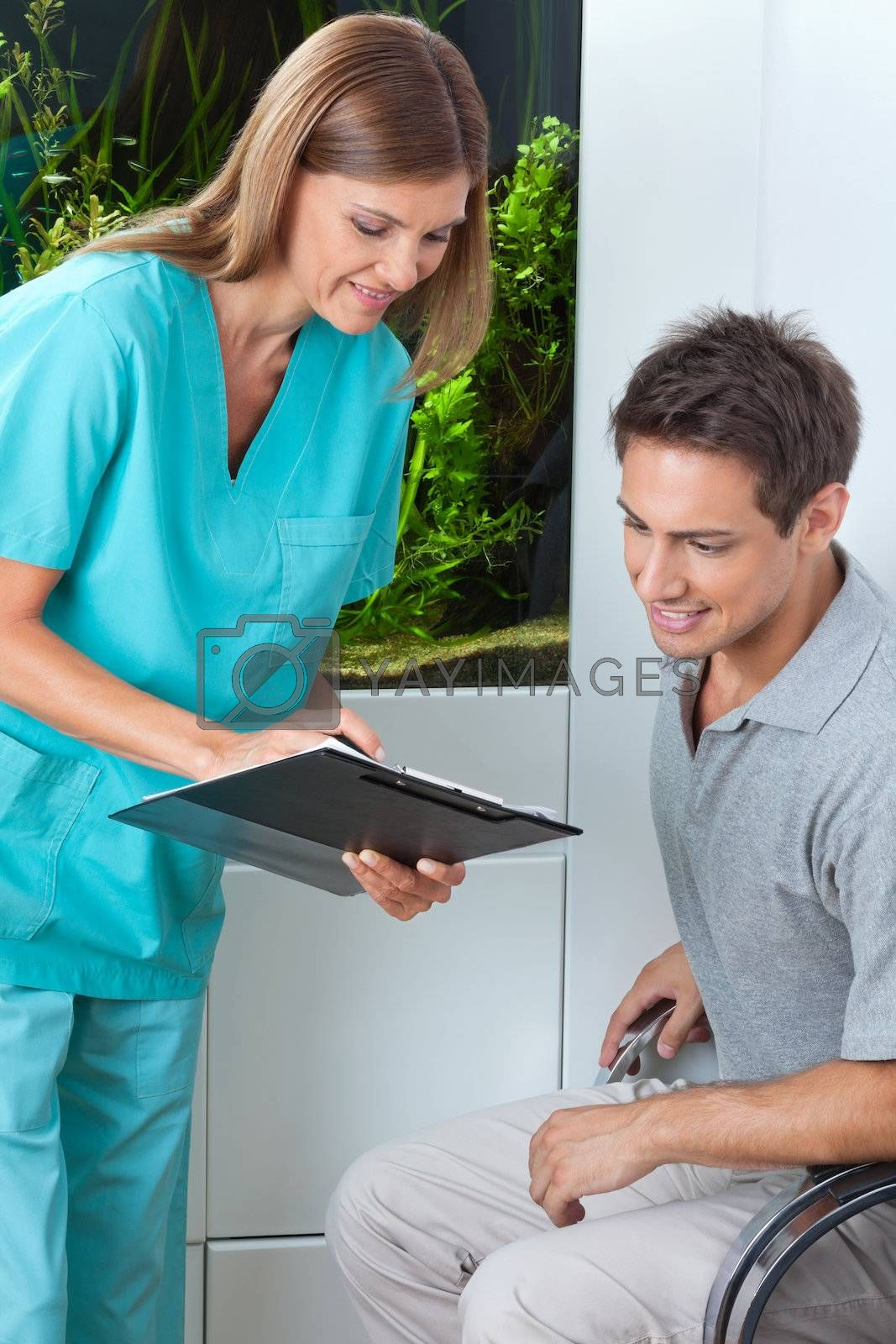 Female dentist taking an appointment of male patient on clipboard at clinic