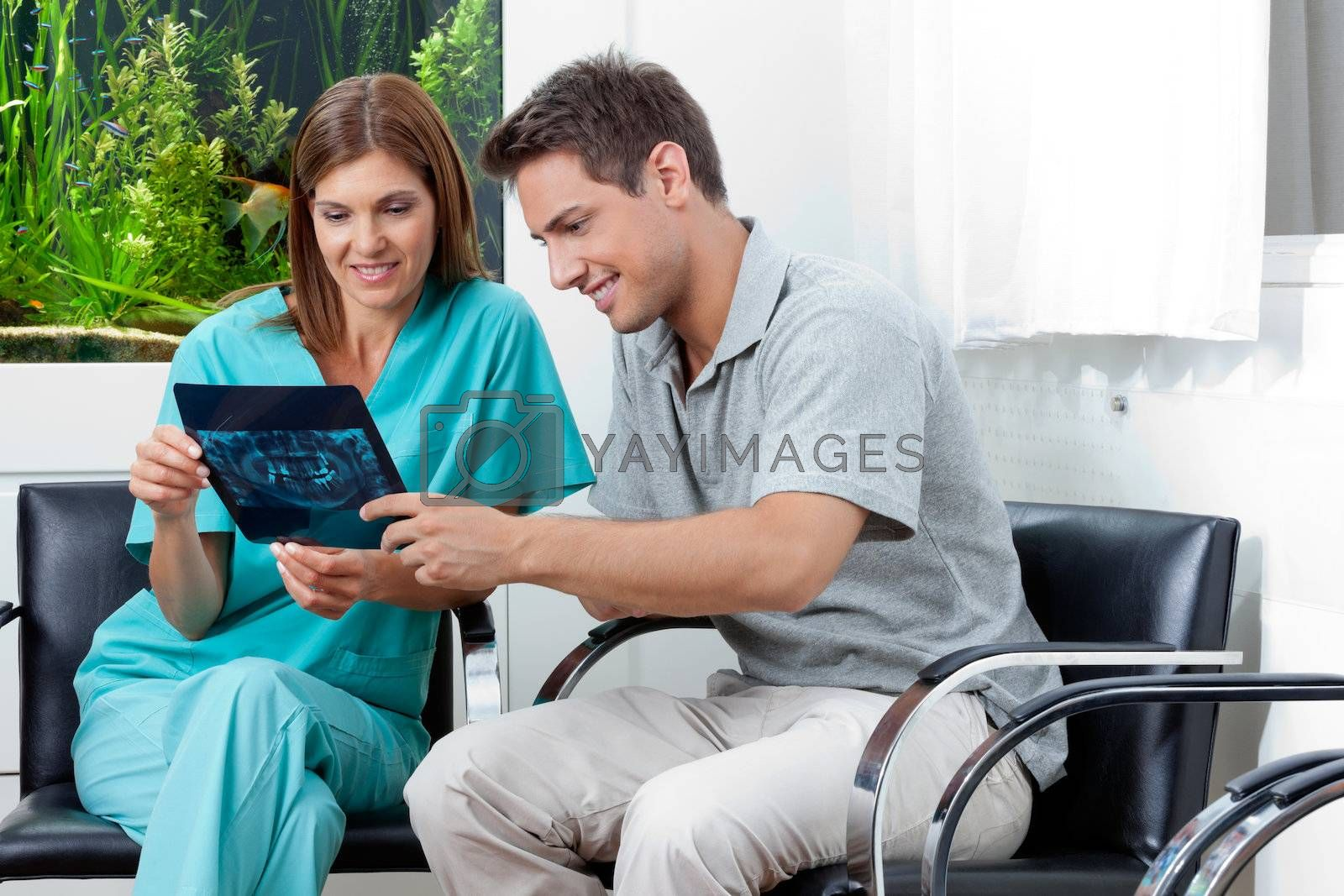 Female dentist showing dental X-ray report to young man in clinic