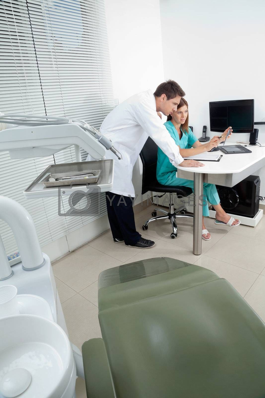 Doctor and female assistant in discussion with dentist chair in foreground