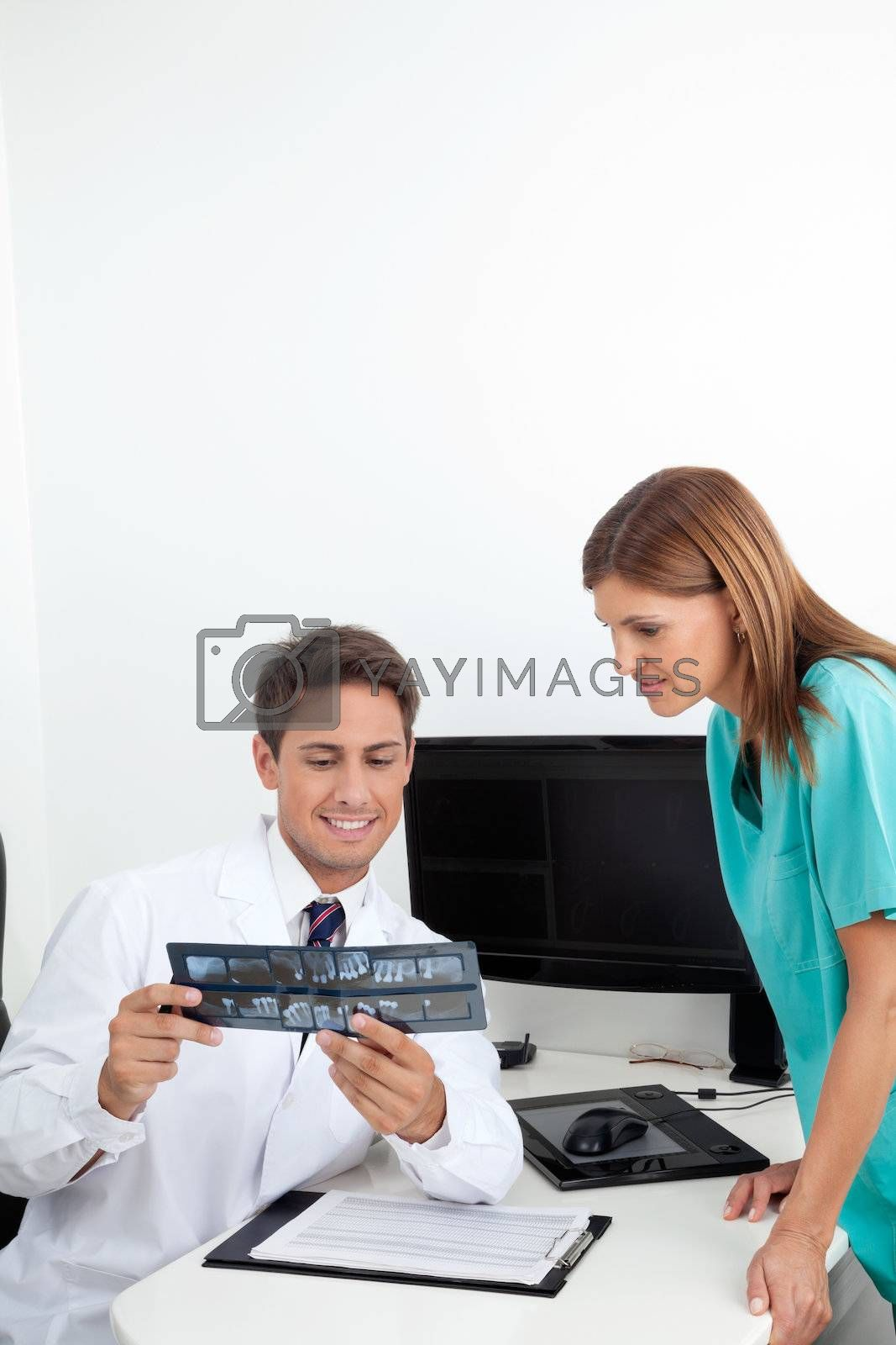 Young dentist and female assistant analyzing X-ray report at office desk