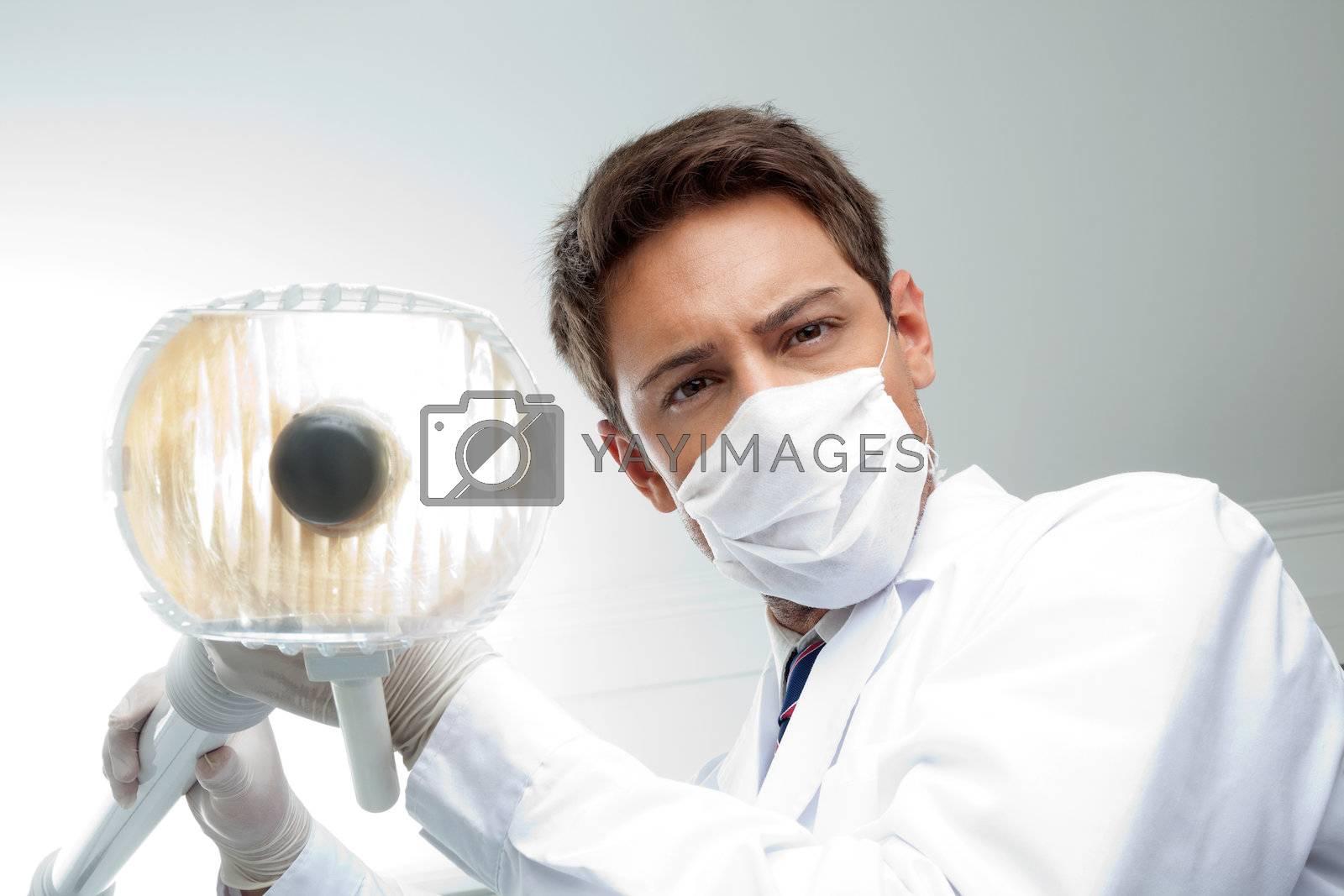 Dentist Holding Dental Lamp by leaf