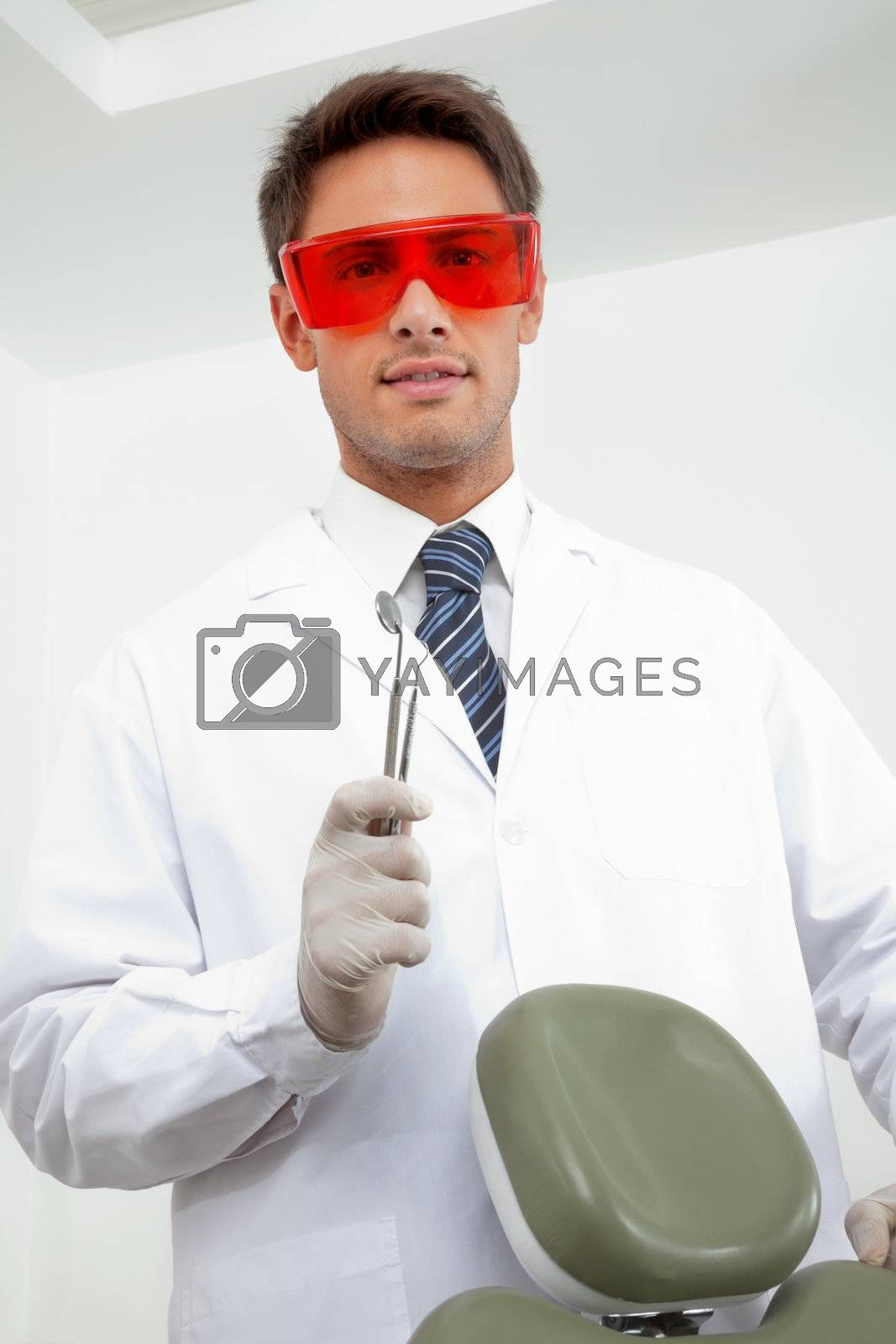 Portrait of young male dentist wearing protective eyewear while holding angled mirror and carver in clinic