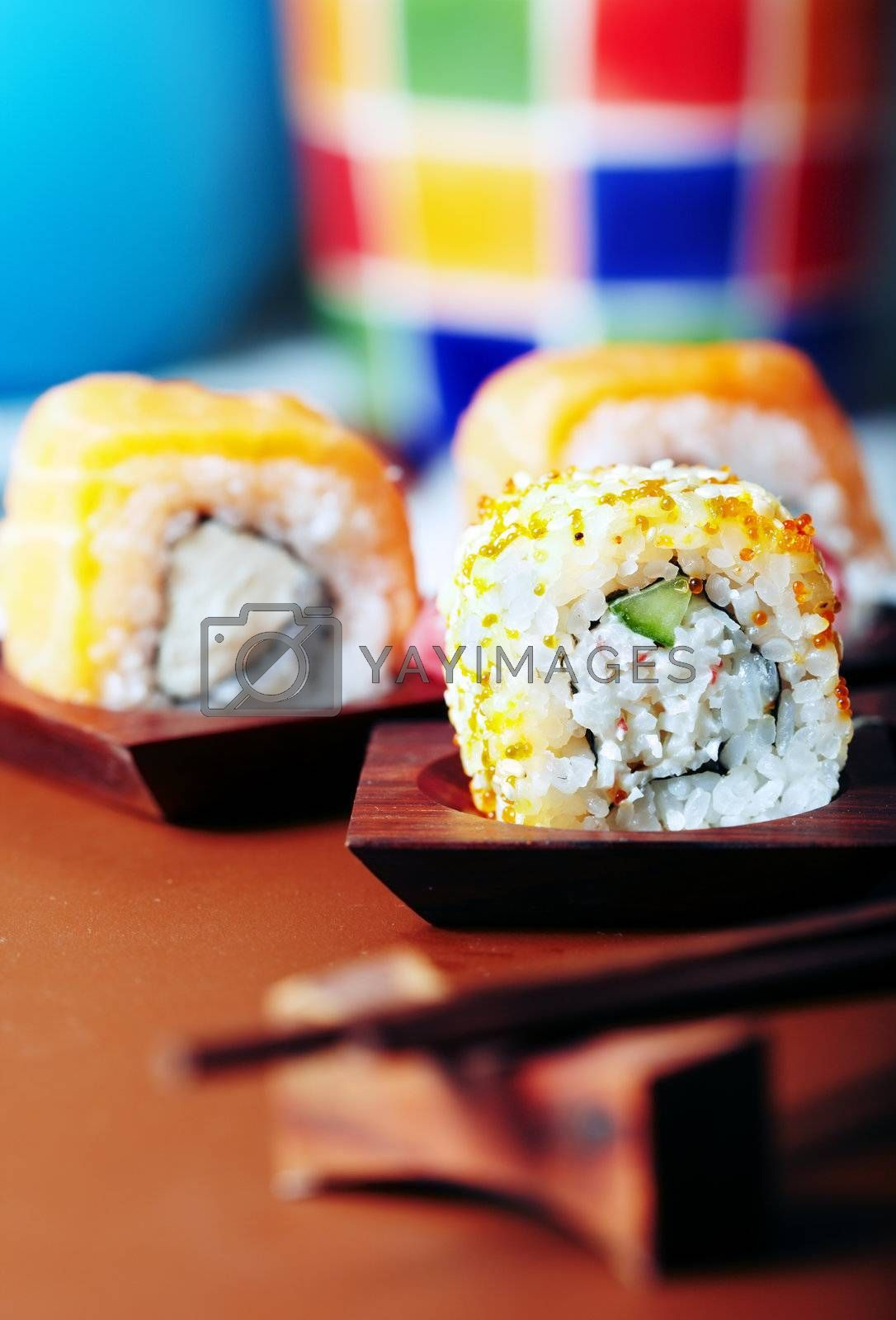 Close-up vertical photo of the rolled sushi with rice and cucumber on the table. Vibrant color and shallow depth of field for natural view