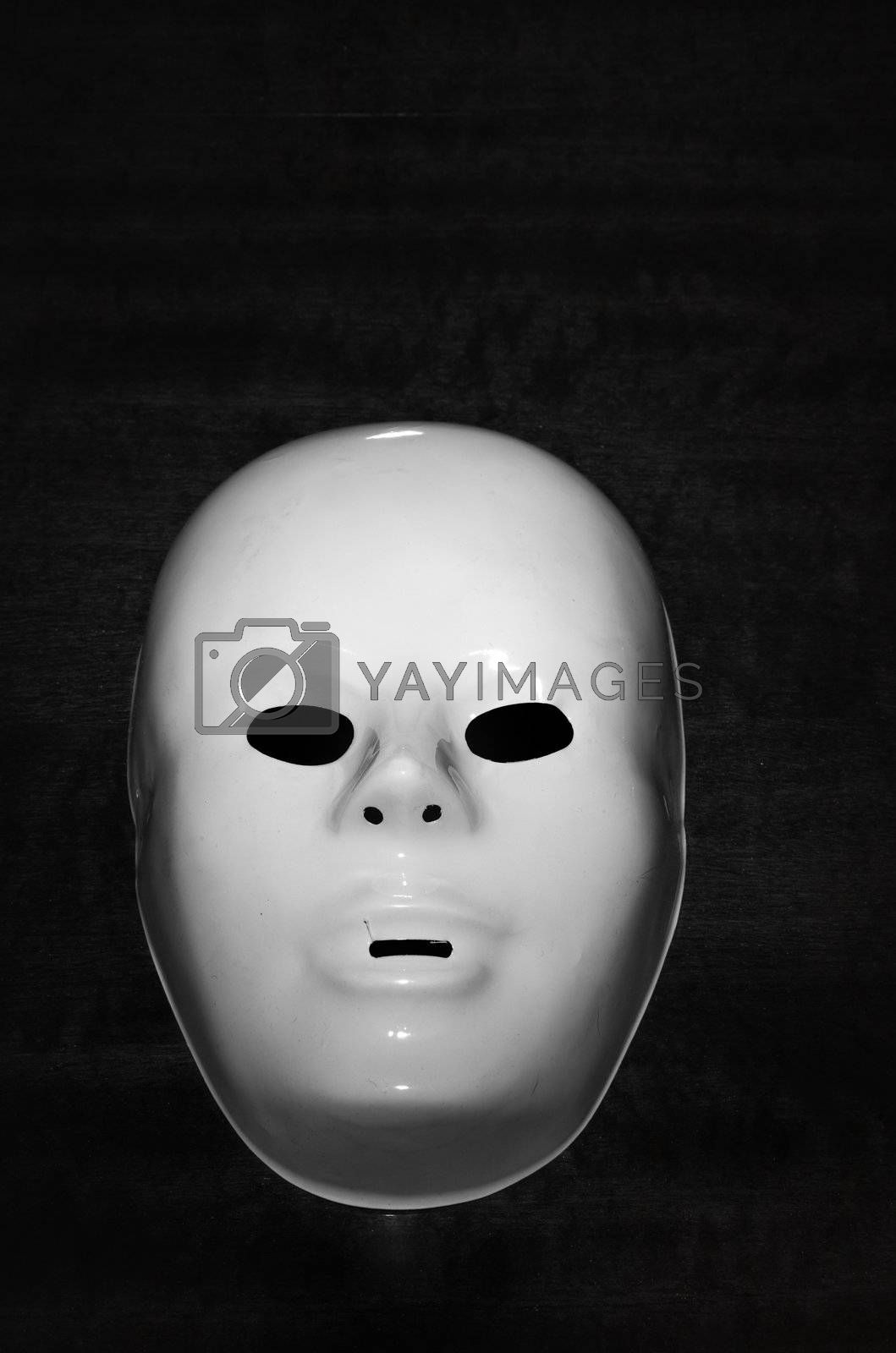 Plastic mask on a dark background as horror symbol