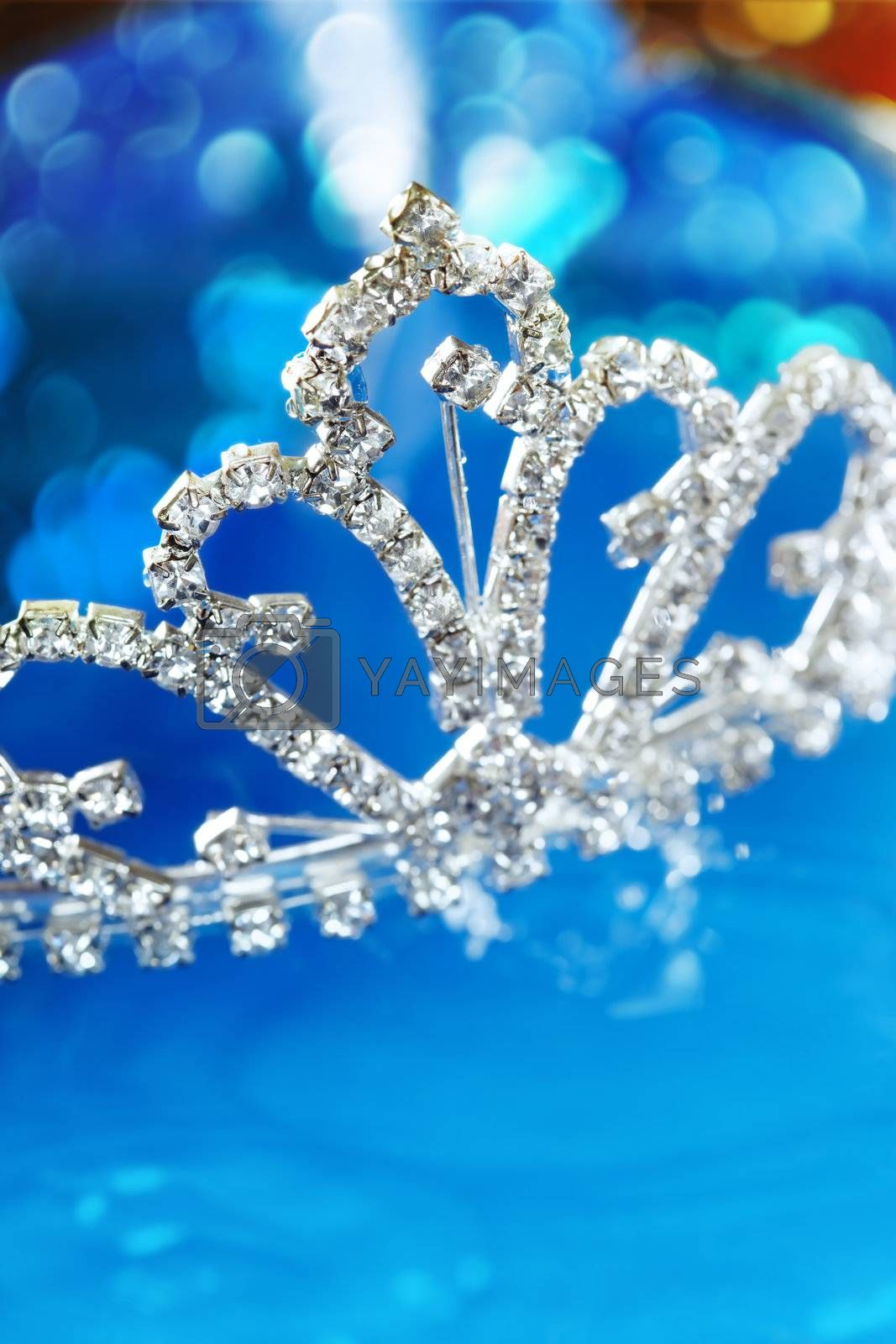 Close-up photo of the silver diadem with diamonds on a blue background with bokeh. Shallow depth of field added by macro lens for natural view