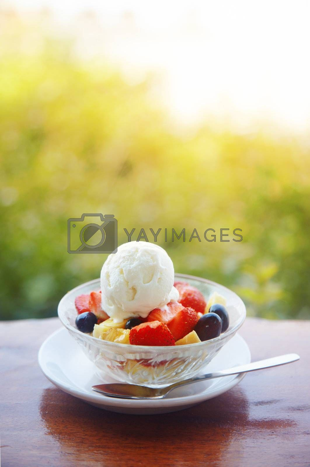 Fruit salad with ice cream on the table outdoors. Vertical photo with shallow depth of field for natural view. Vibrant colors