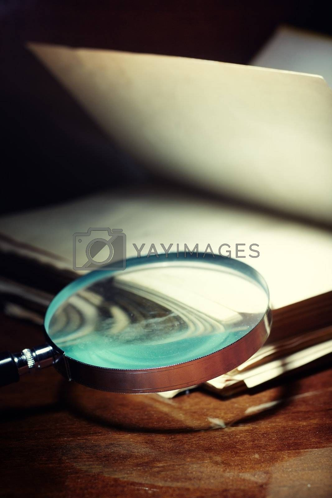 Old book and magnifier on a dark background as a symbol of scientific study