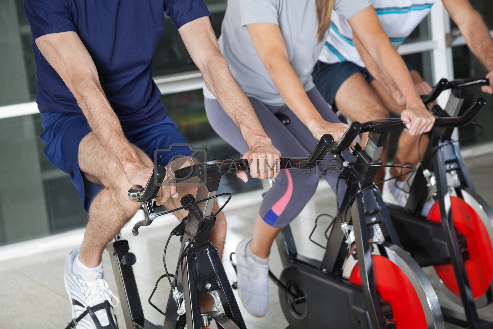 Low section of men and woman on exercise bikes in health club