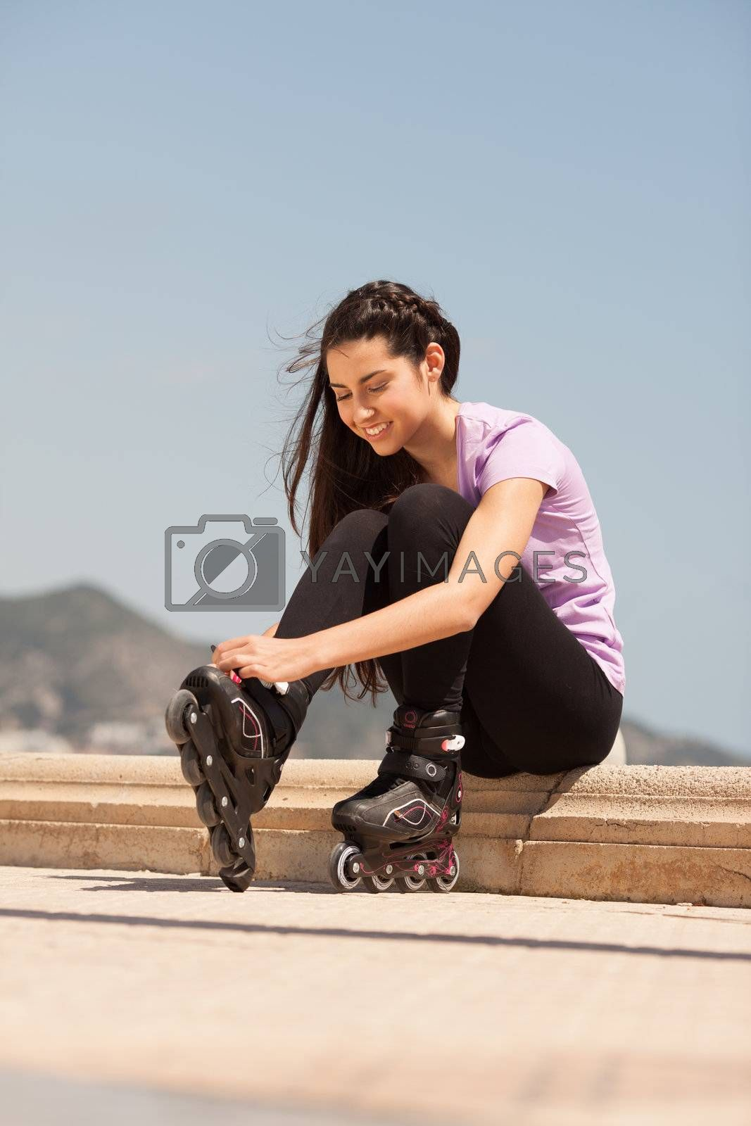 Girl going rollerblading sitting putting on inline skates outdoors