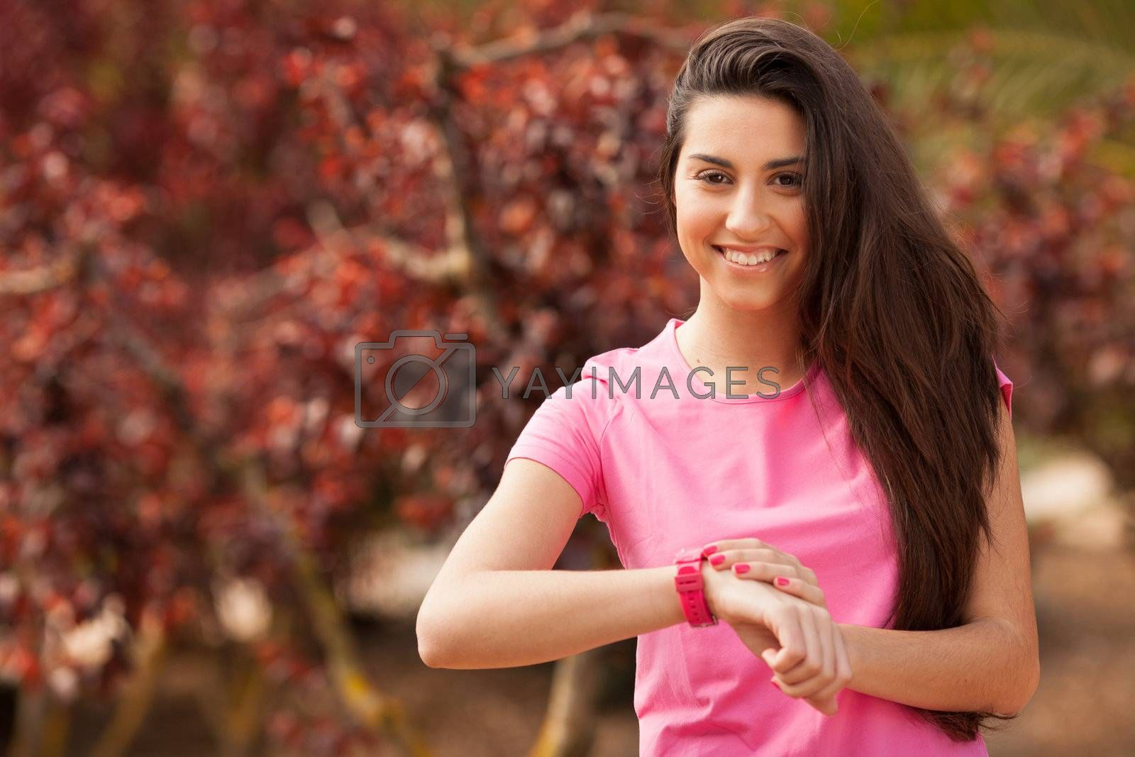 Sport woman checking heart rate in pink watch