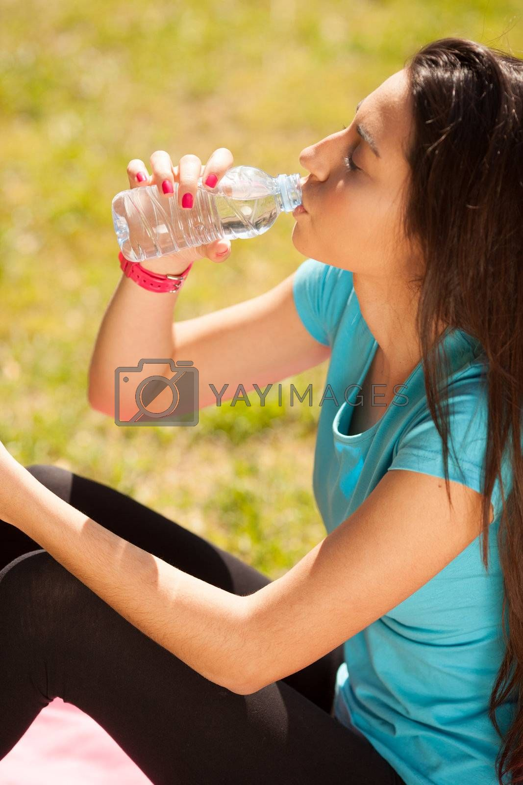 young beautiful sport woman drinking water after sport outdoors