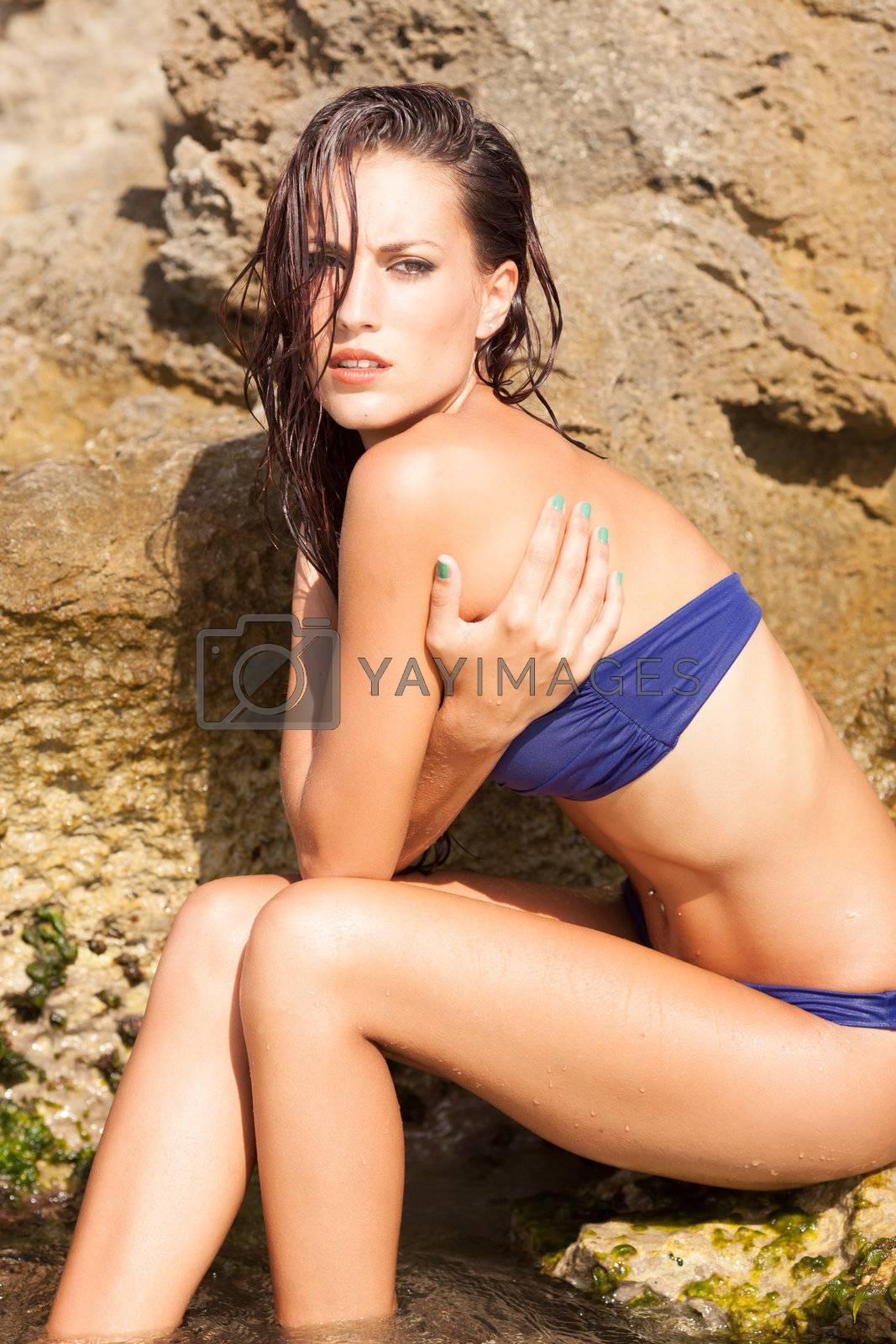 Portrait of sexy model enjoying a bath in the ocean with rocks