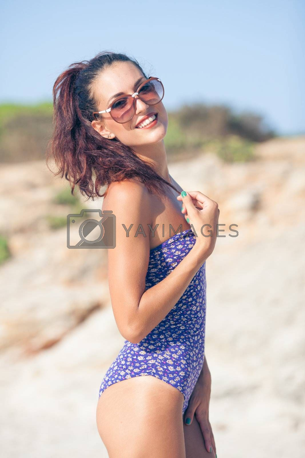 Sexy vintage model in swimsuit posing on the beach with glasses