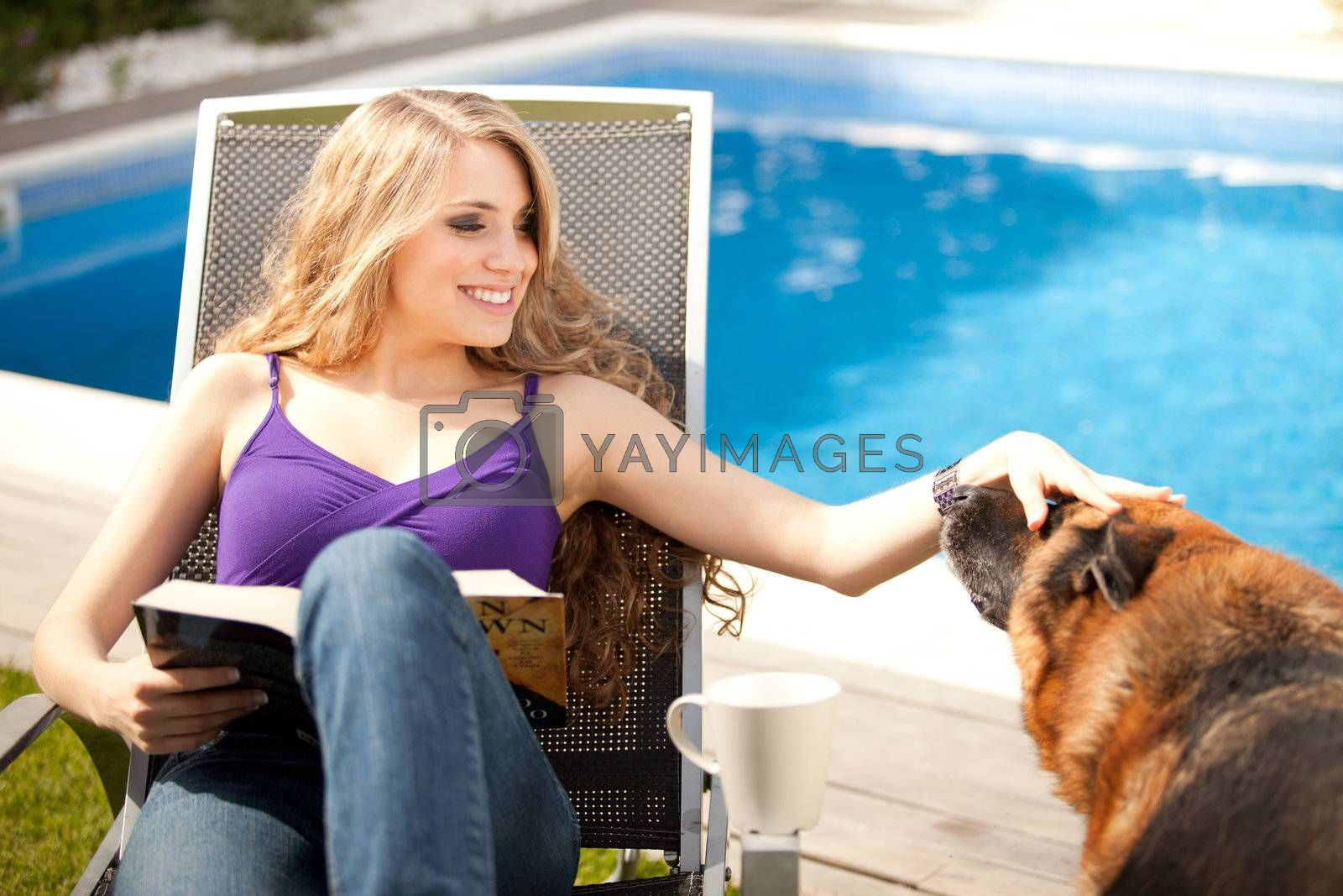 young beautiful woman playing with dog outdoors